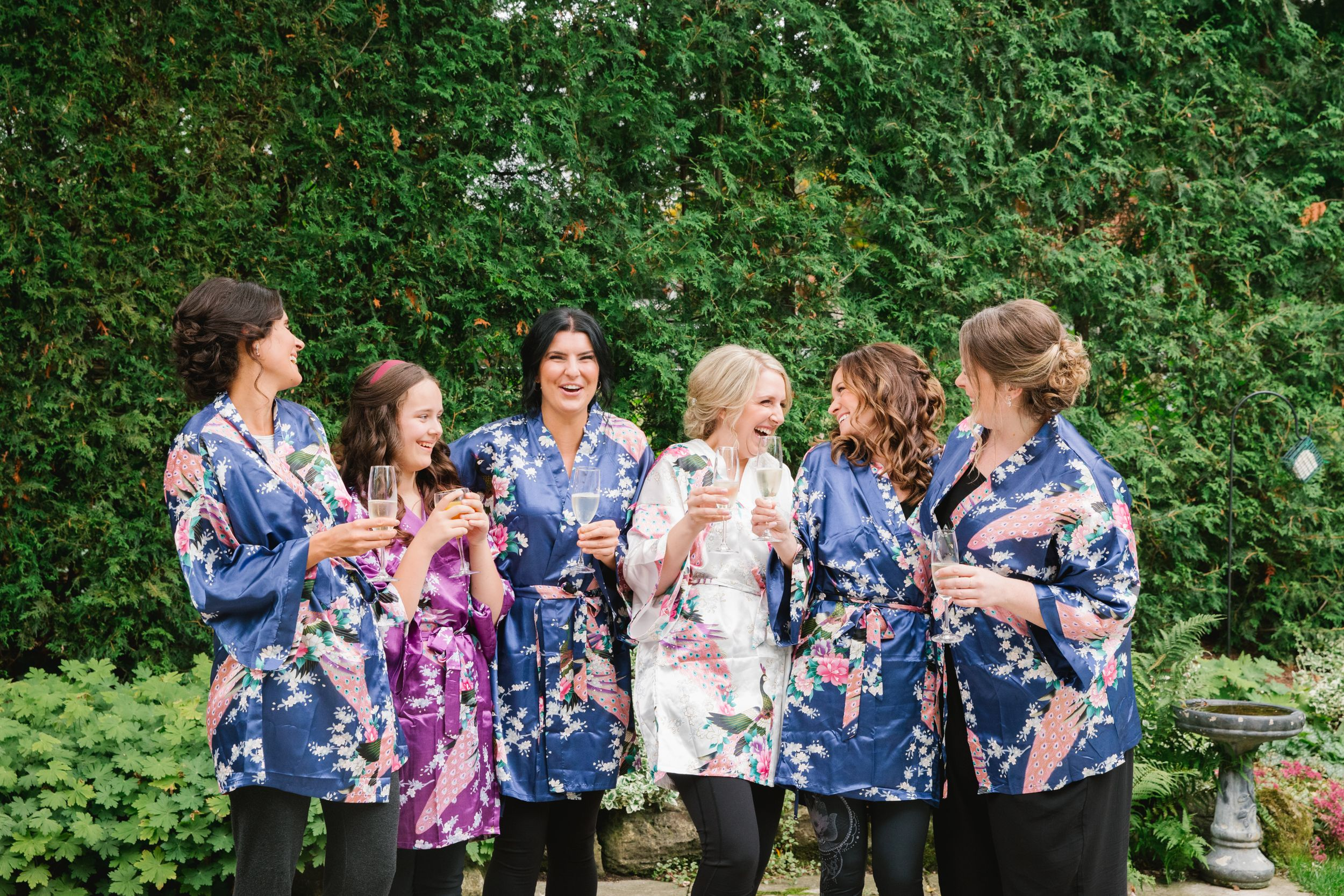 bride and bridesmaids in colourful robes holding champagne and laughing in backyard