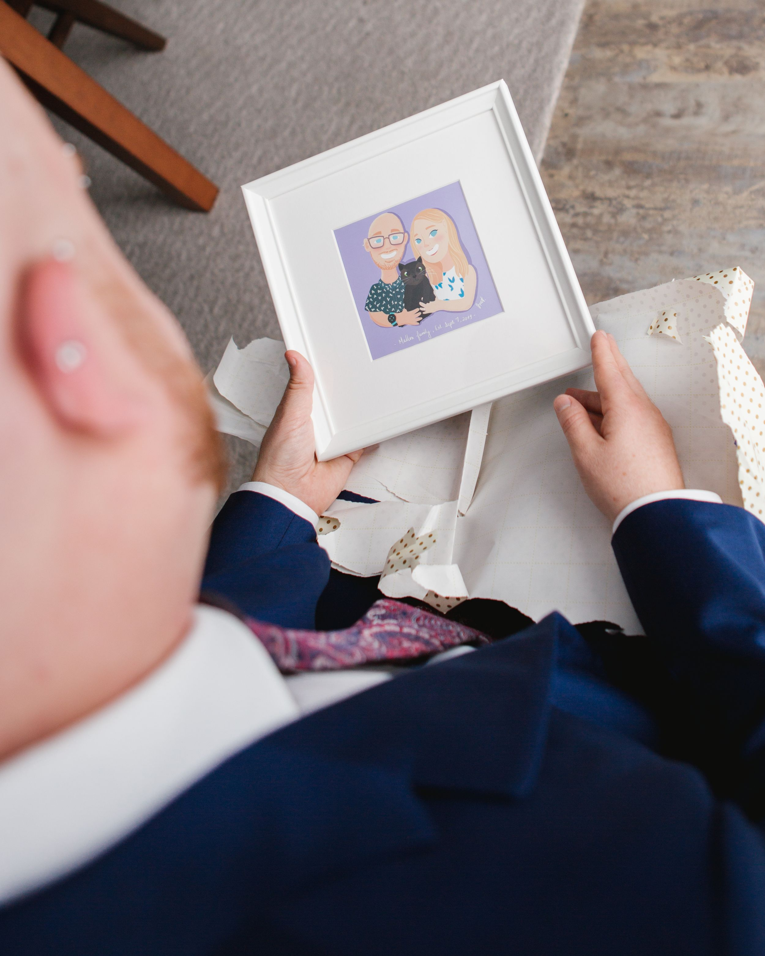 groom looking at a cartoon portrait of him and his fiance