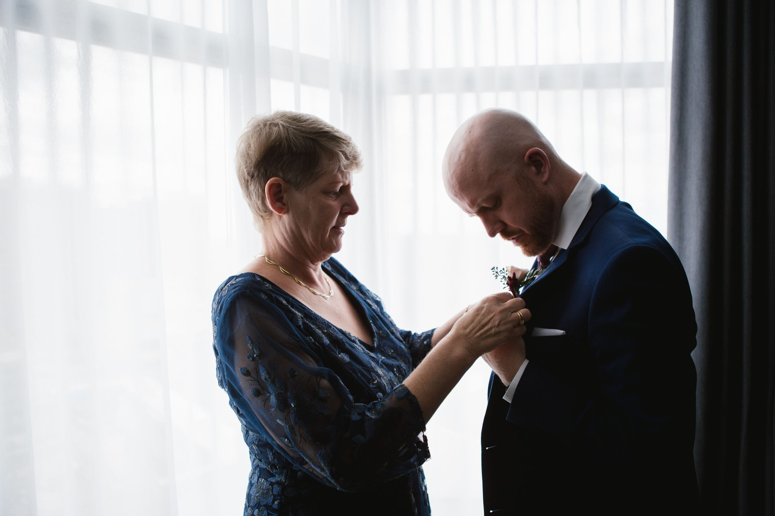 mother of groom in blue dress helping with boutonniere