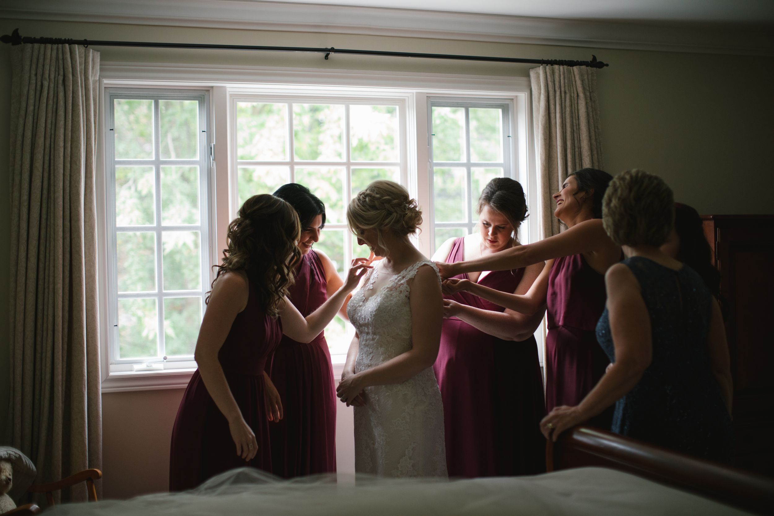 bridesmaids in burgundy dresses helping bride into her wedding dress against the window
