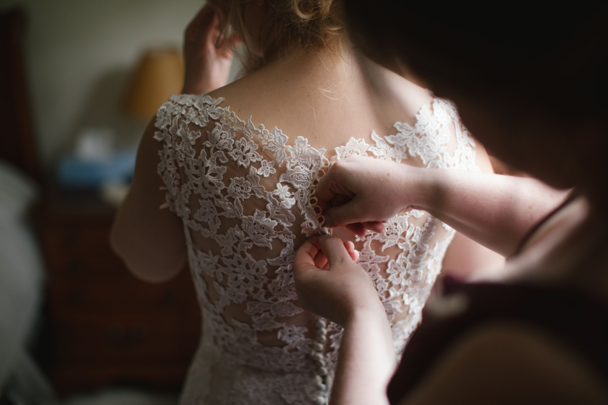 close up of bridesmaid buttoning up wedding dress in thornhill