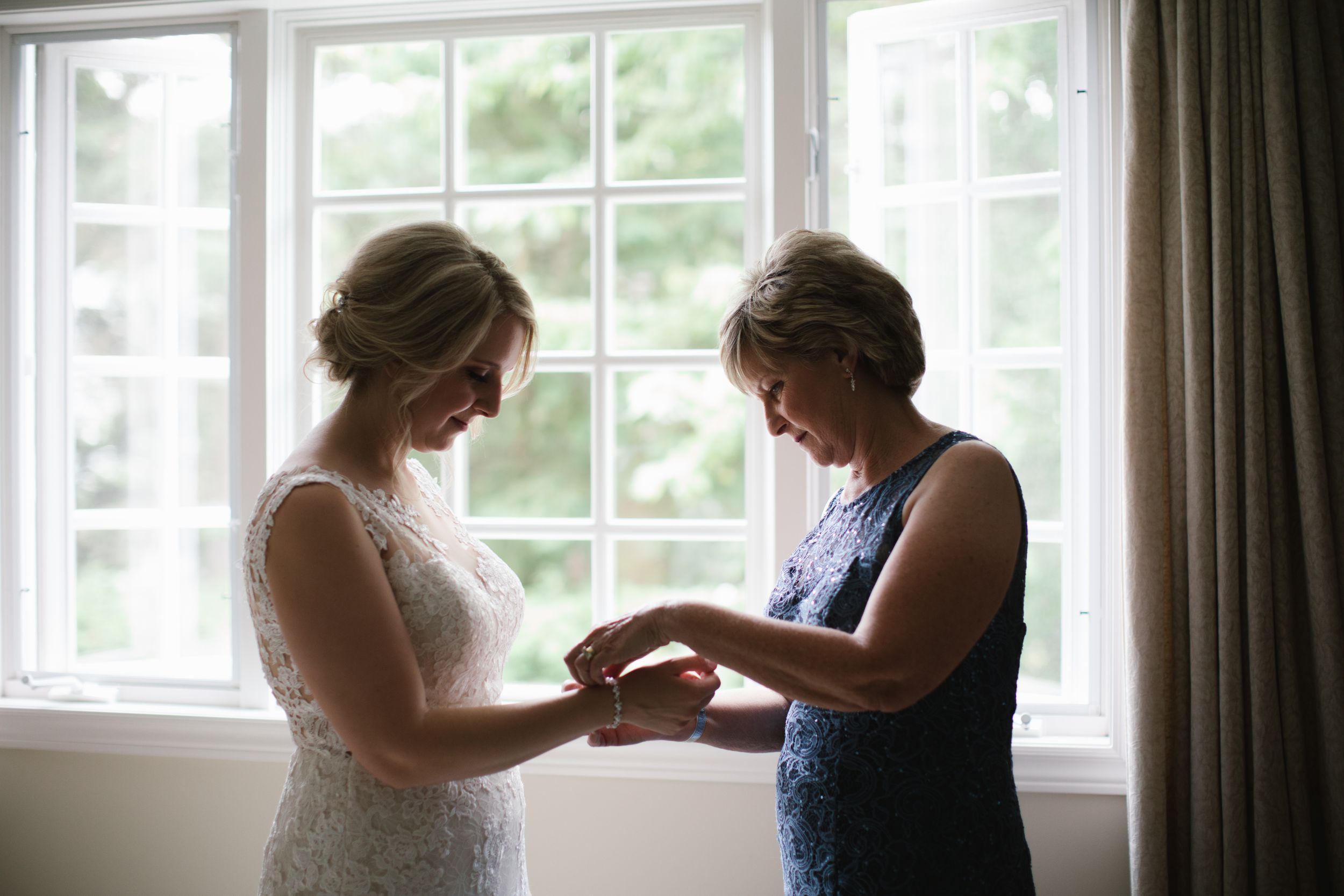 mother of bride helping bride put on her jewelry against the window