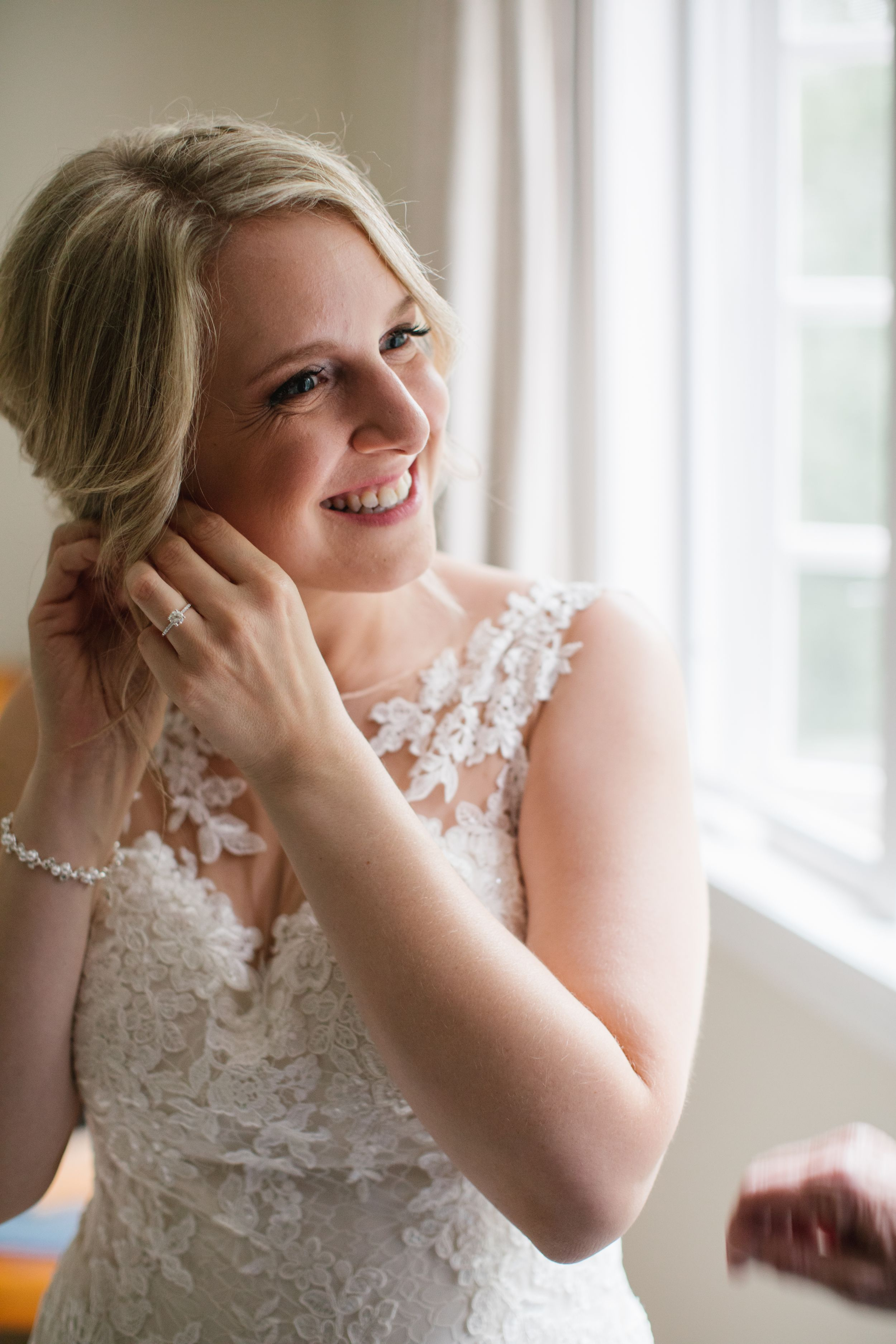 bride smiling while putting on her wedding earrings