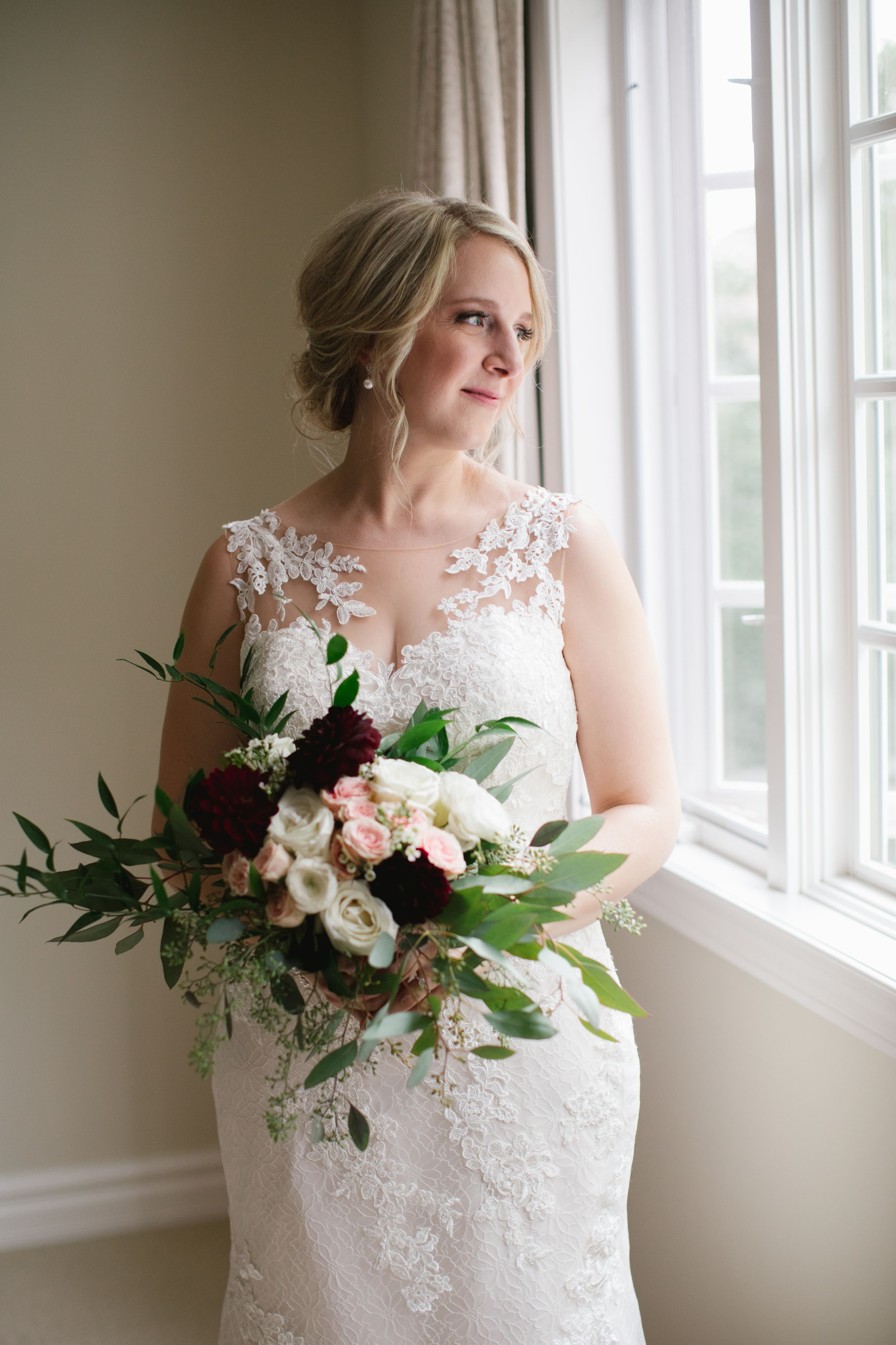 bride holding her burgundy and pink bouquet and looking out of the window