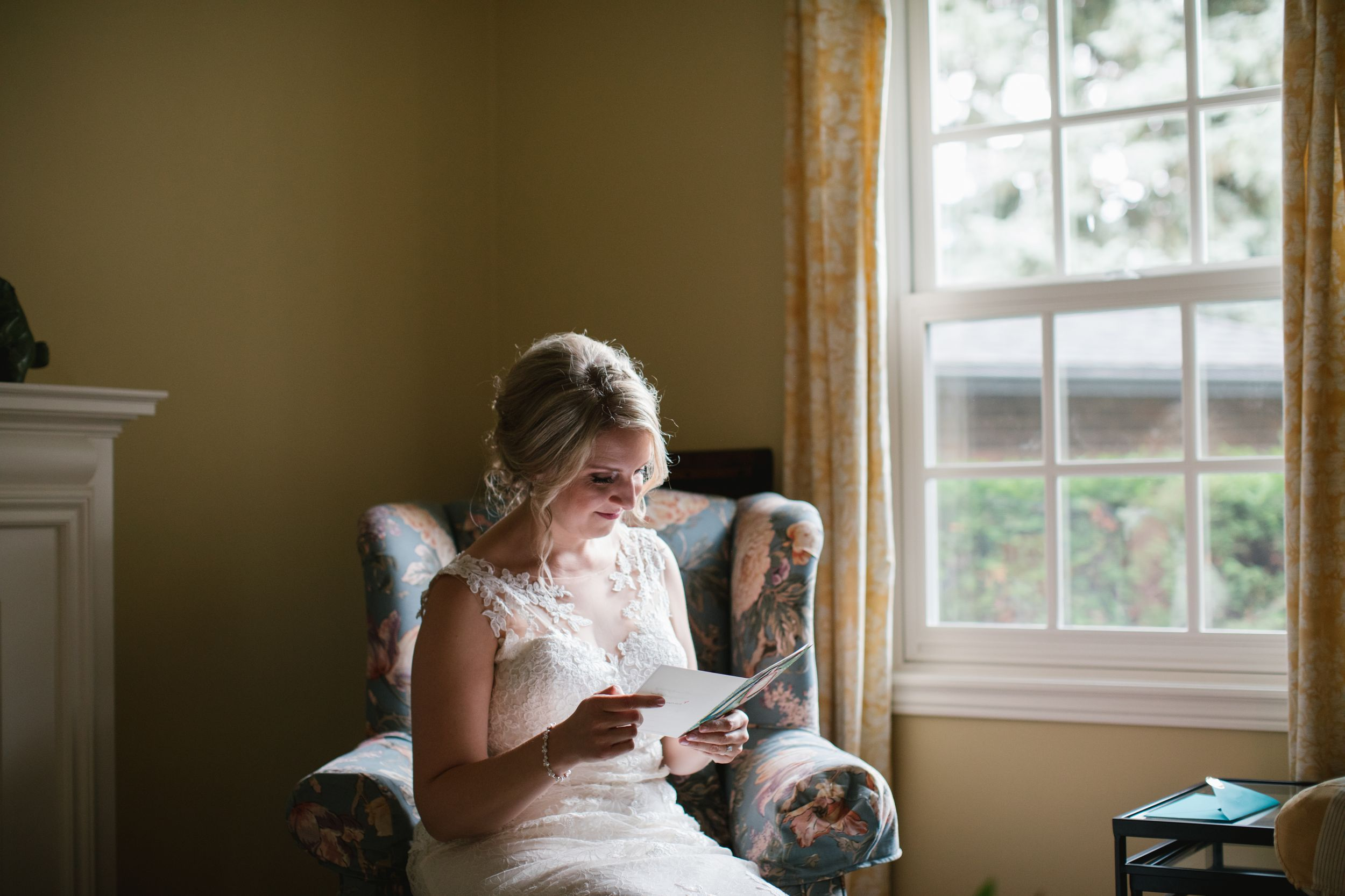 bride sitting in living room chair and opening her groom's letter