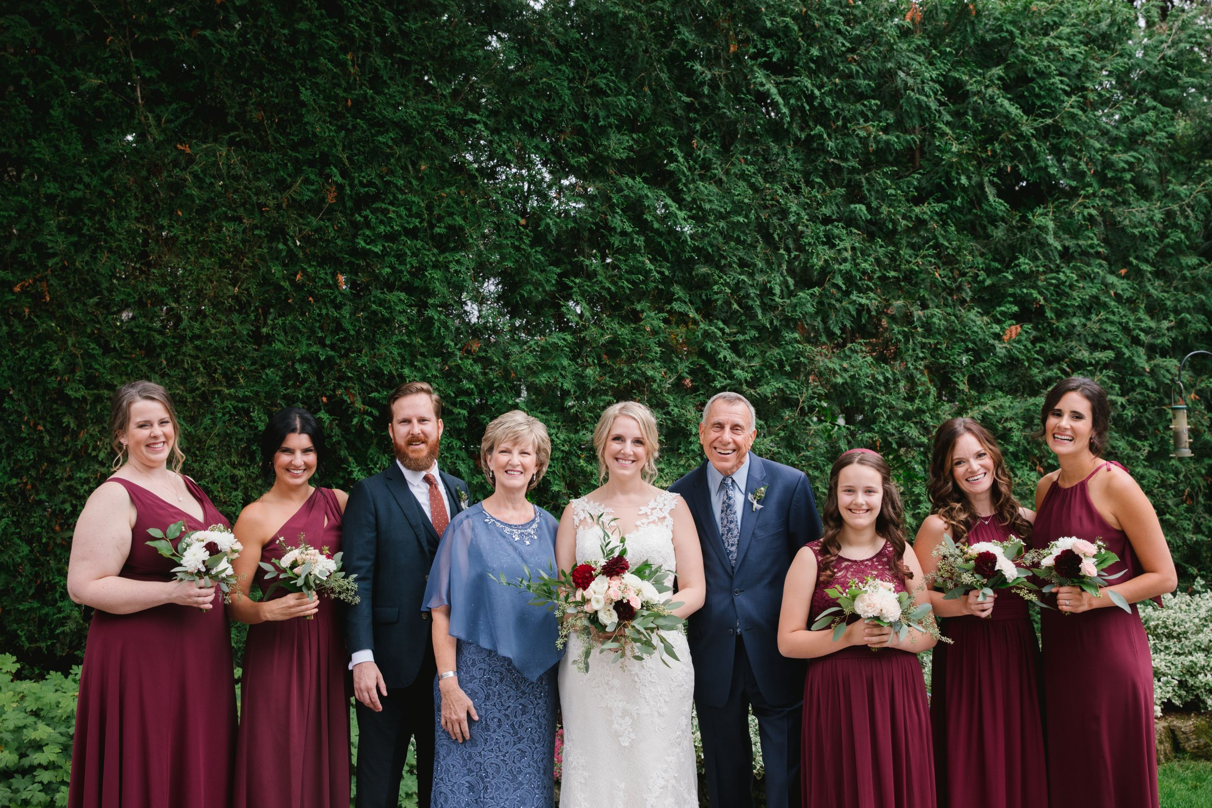 bridesmaids and parents of the bride with bride smiling in backyard