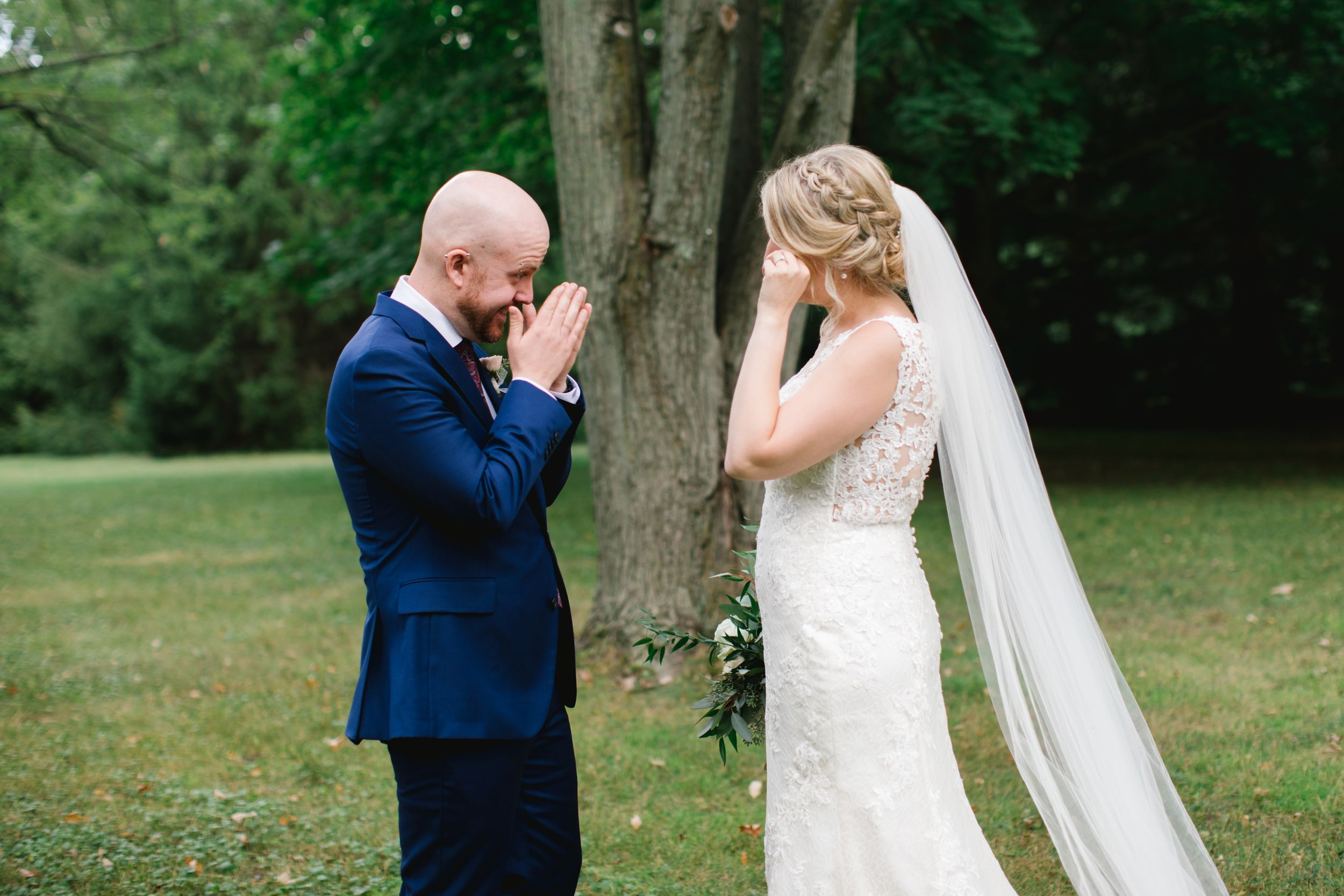 bride and groom wiping away tears after first look in park