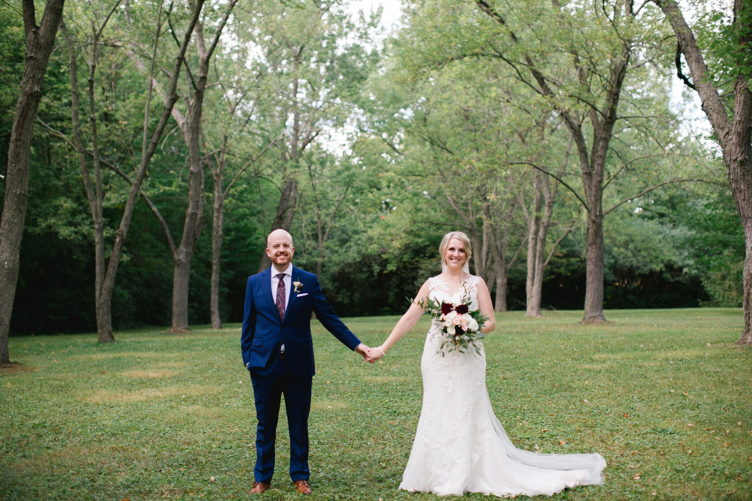bride and groom holding hands and smiling in park toronto