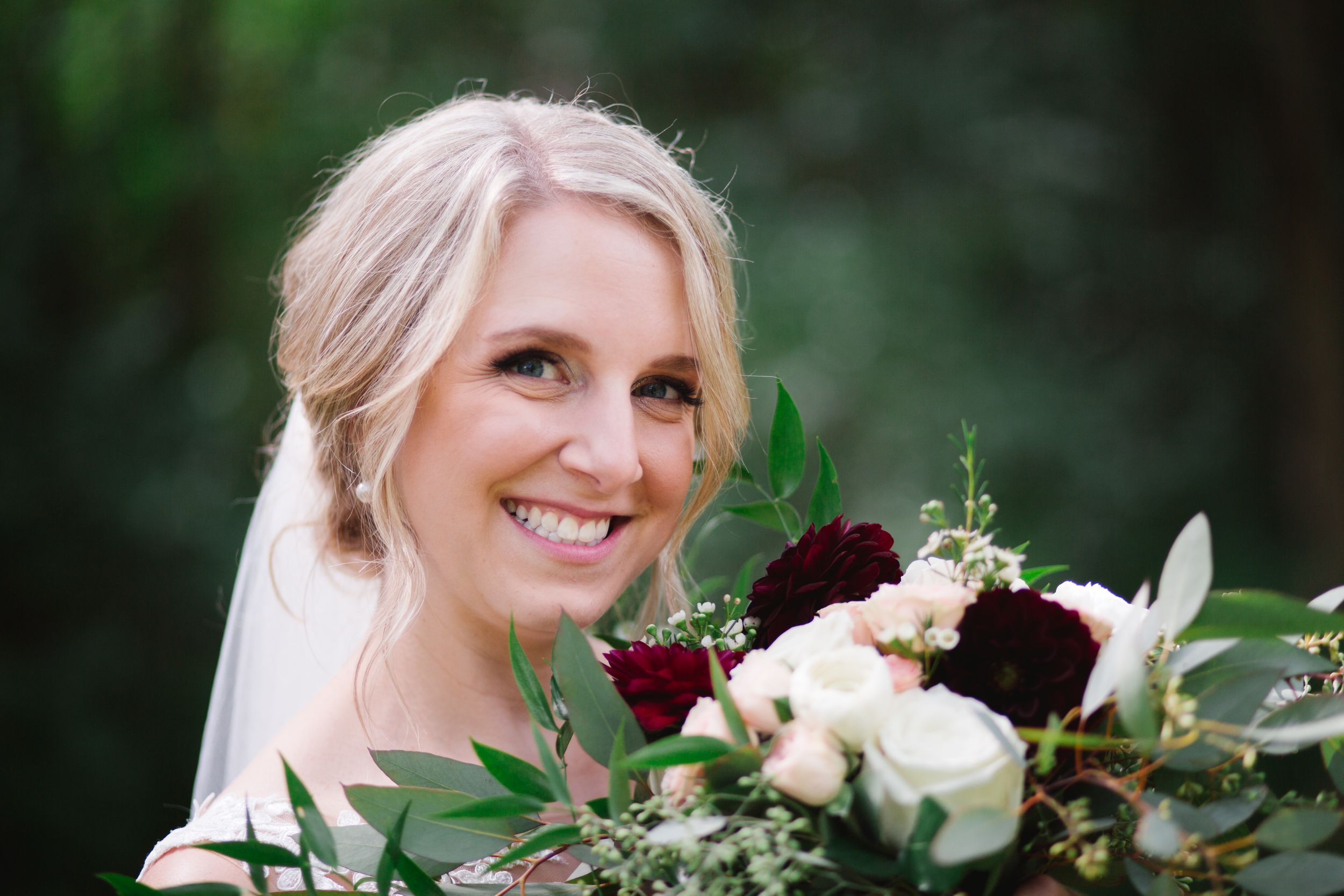 blonde bride smiling at her bouquet of burgundy and pink flowers