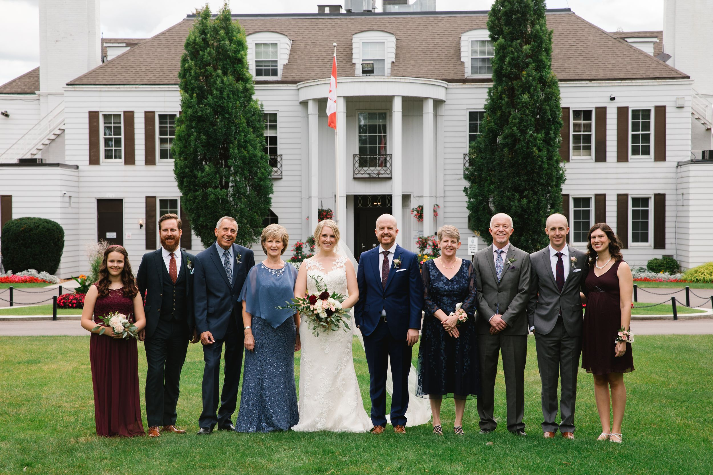 bride and groom with family in front of white building shouldice hospital wedding