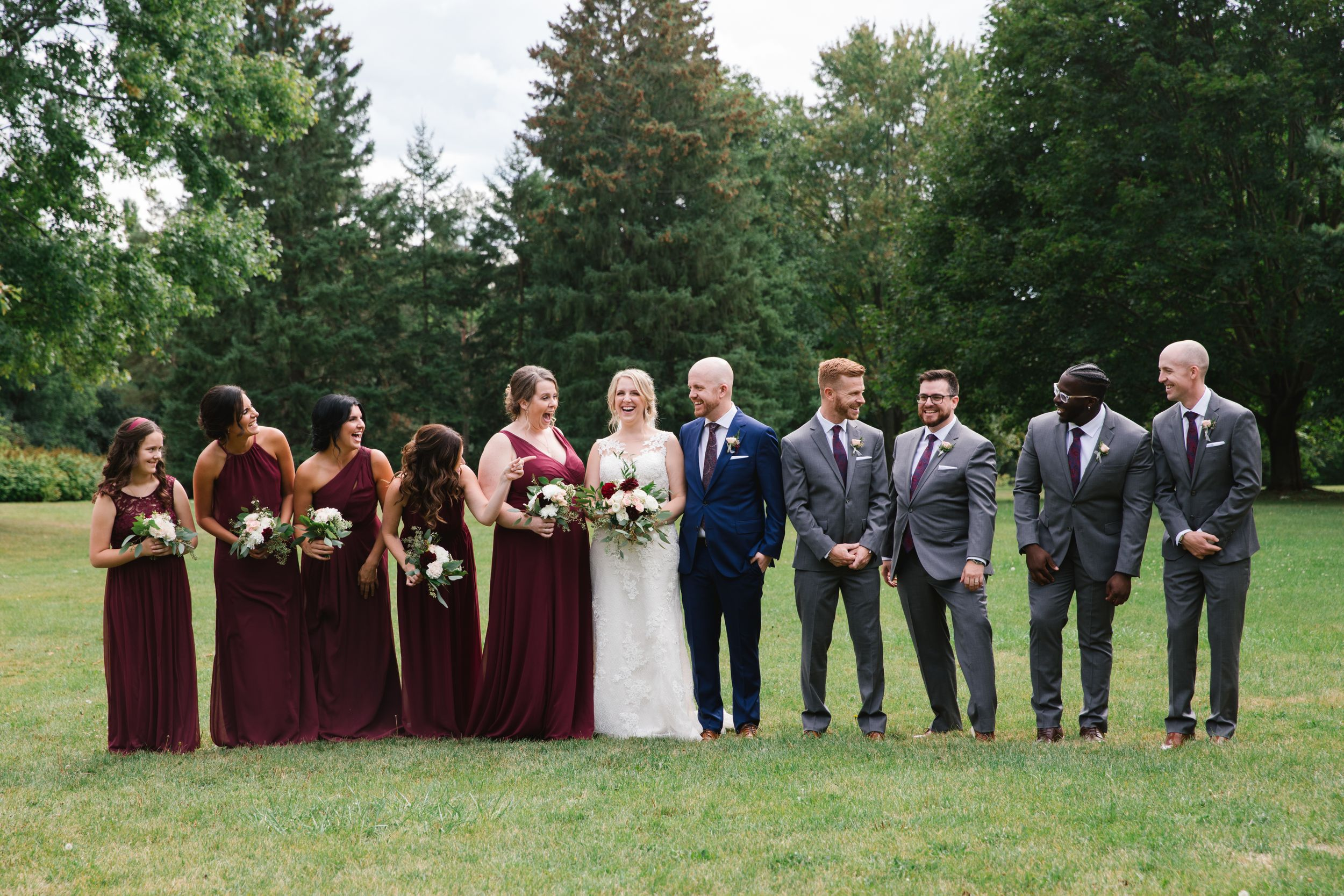 bridal party looking at each other and laughing in park