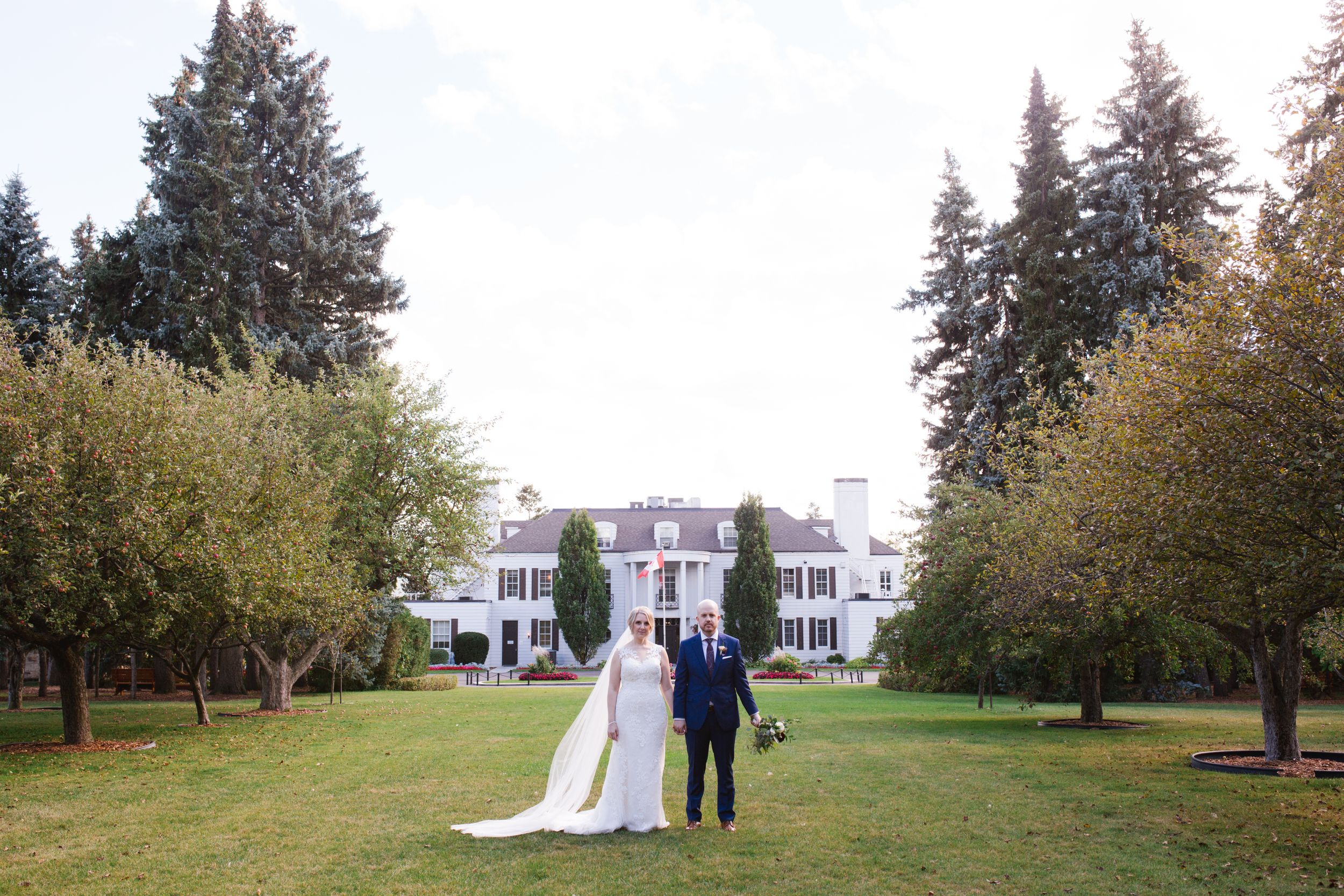 bride and groom in front of white building with columns and trees on either side shouldice hospital thornhill