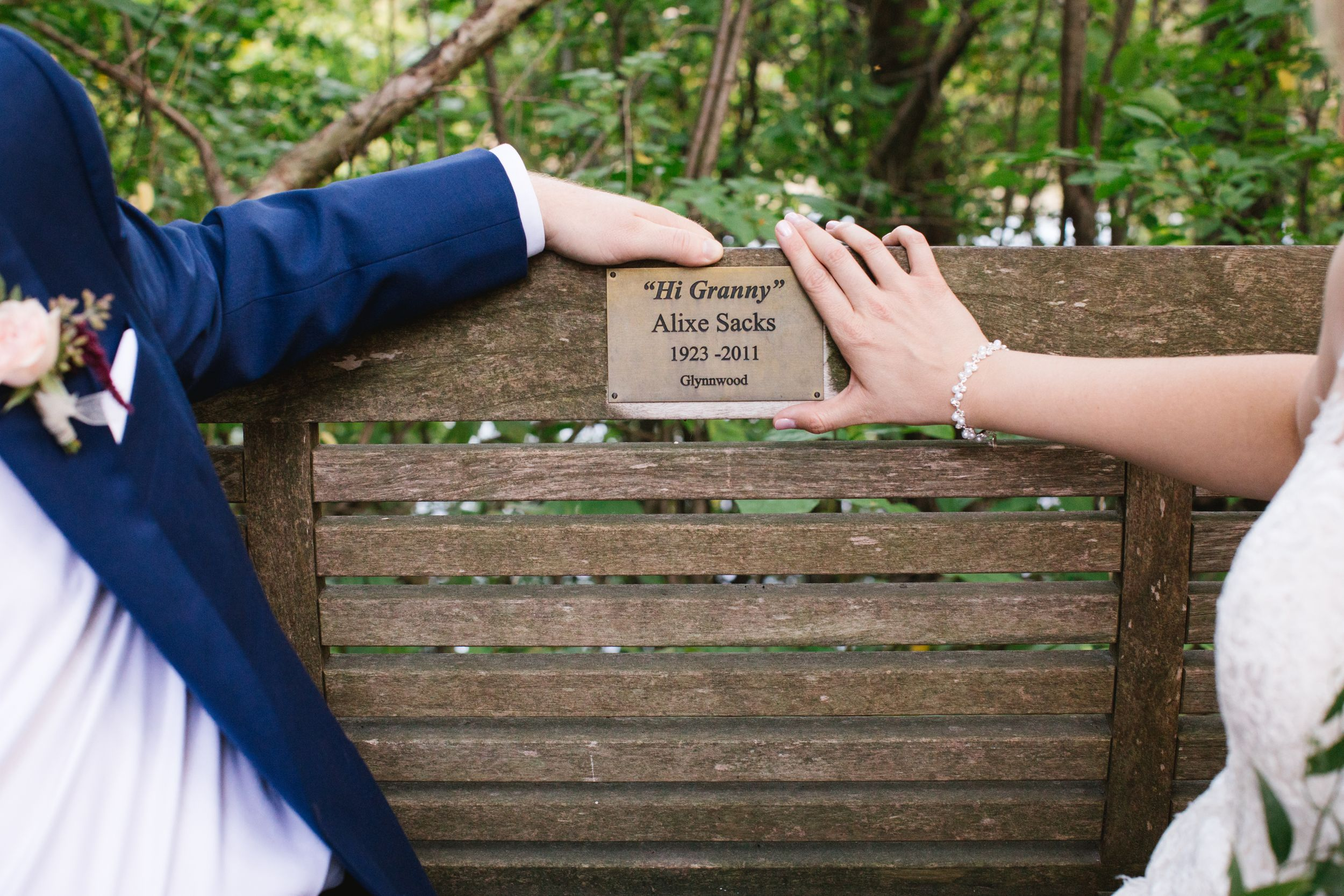 bride and groom holding plaque of relative that passed away on park bench