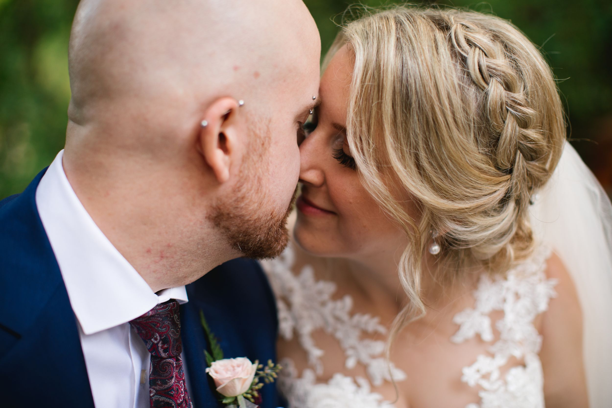 close up of bride and groom kissing wedding hairstyle braid greenery in toronto