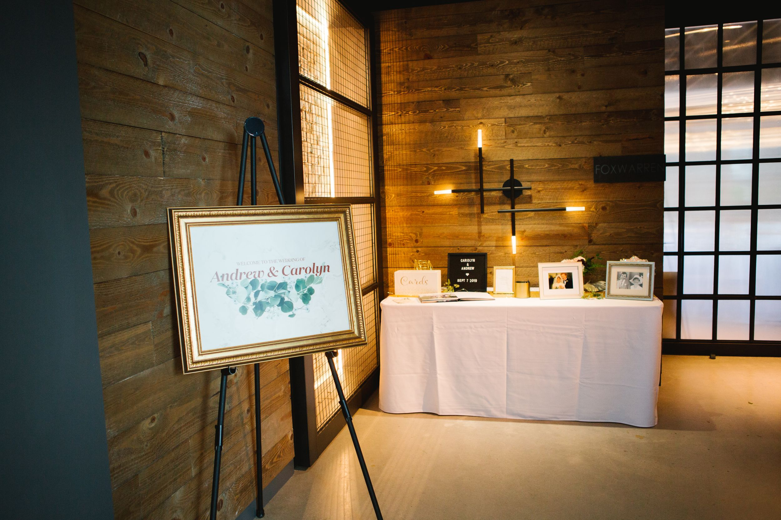 reception entrance set up, gold sign and signing table in wooden industrial room village loft events