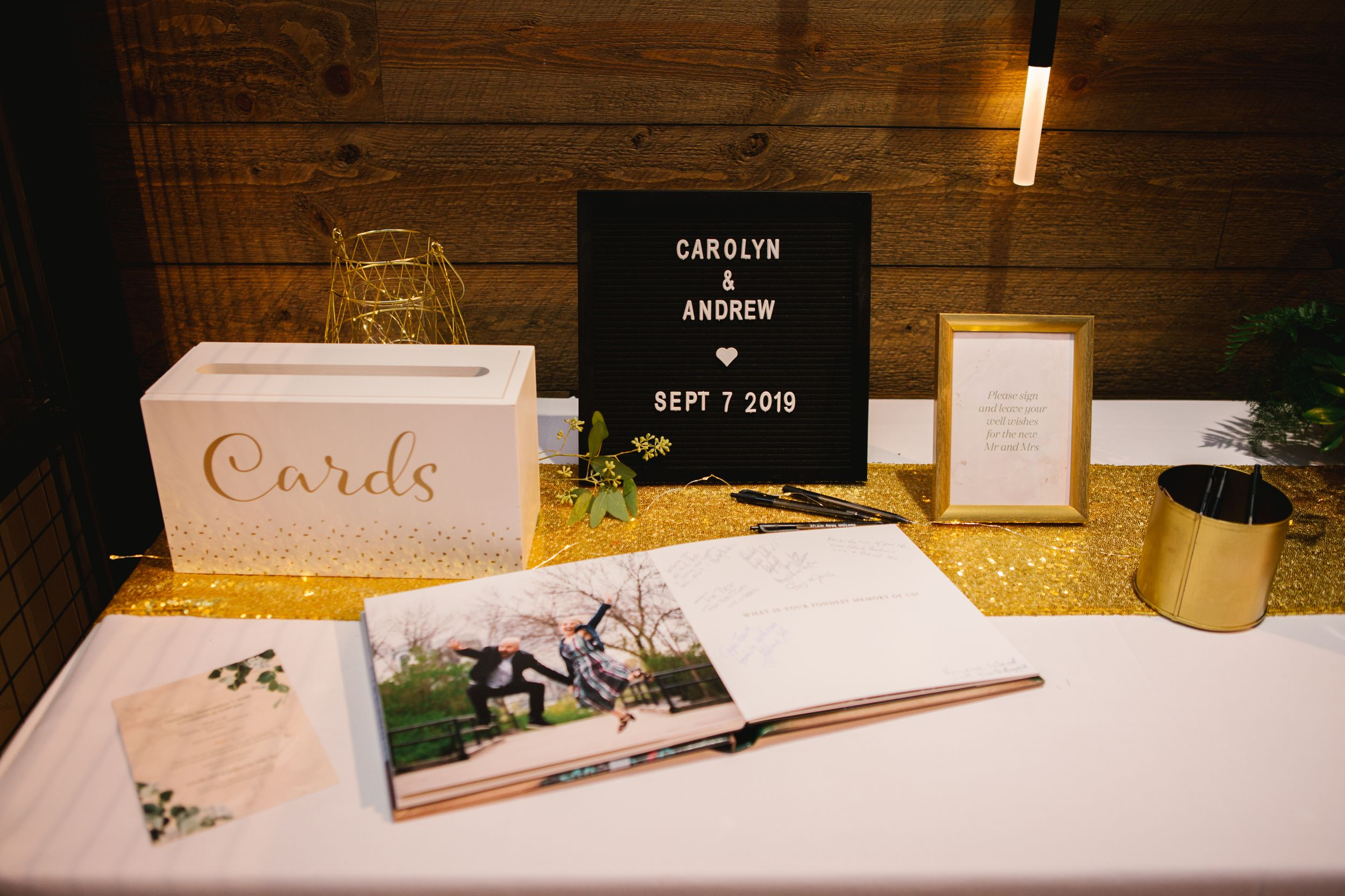 cards table with black felt sign and guest signing book with gold accents wedding