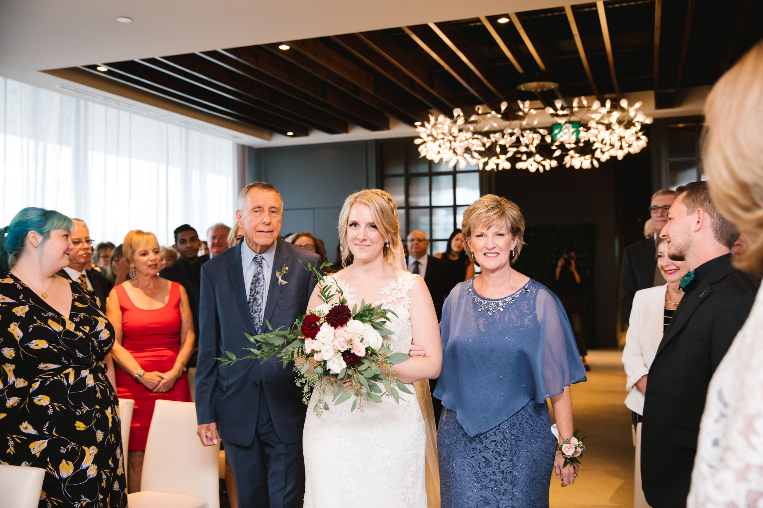 bride walking down aisle with both parents and holding a bouquet of burgundy and pink flowers