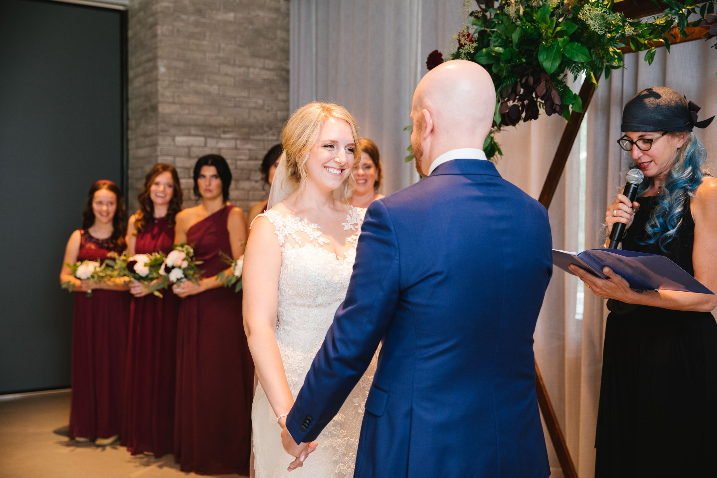 bride looking at groom and smiling with bridesmaids behind her during wedding ceremony