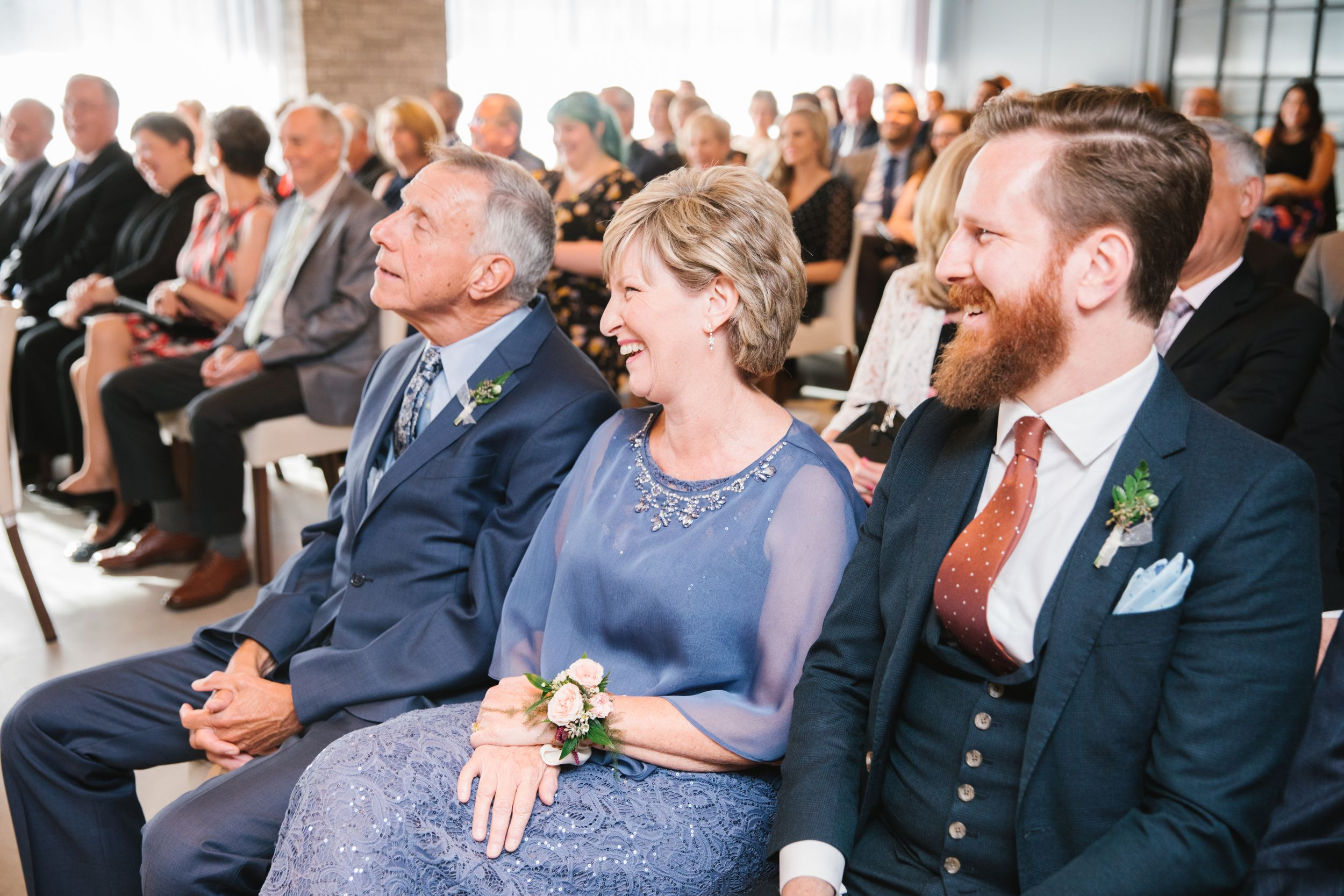 mother of bride sitting in audience and laughing during ceremony