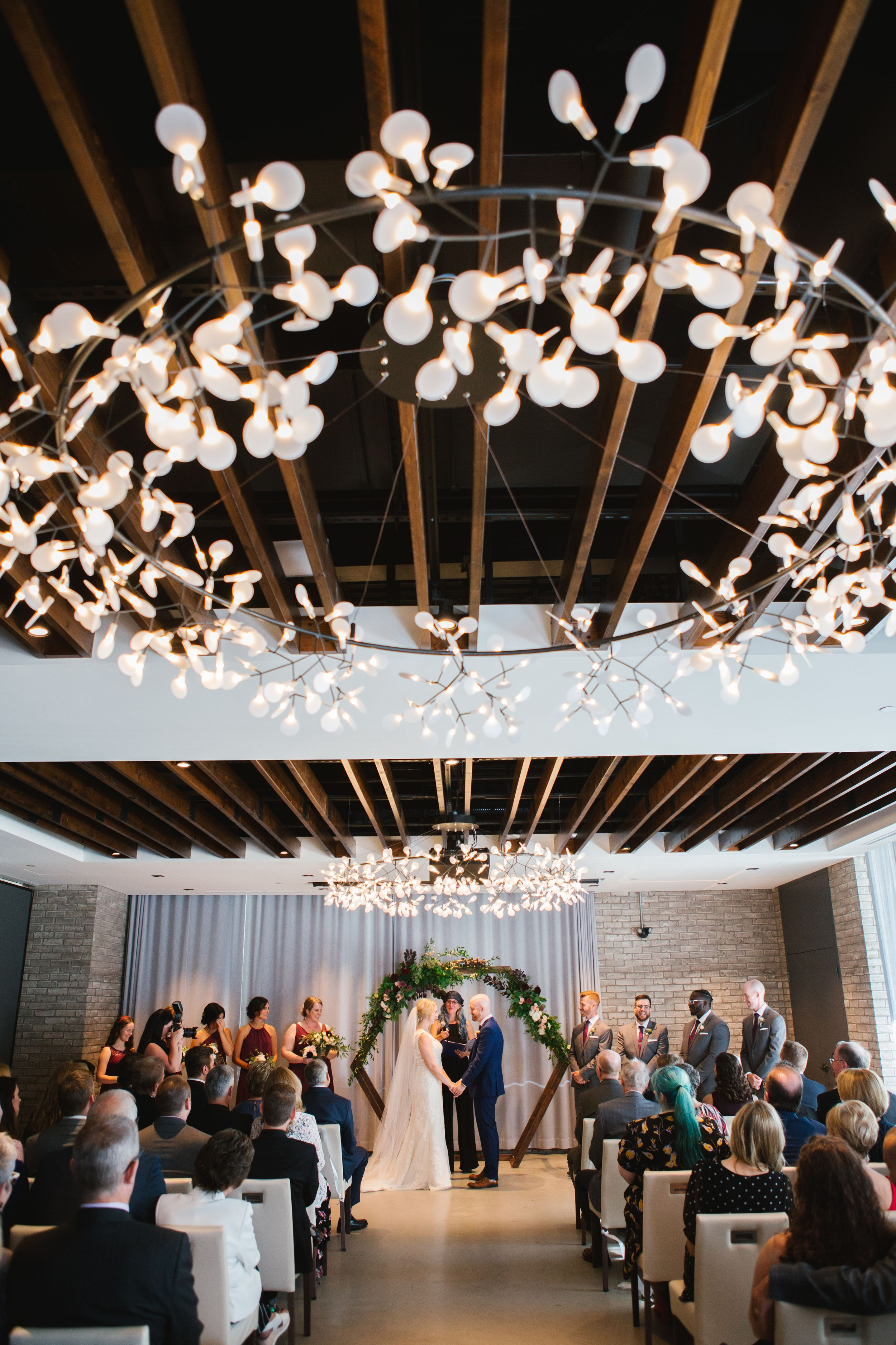 bride and groom holding hands at the altar with light installation above indoor ceremony