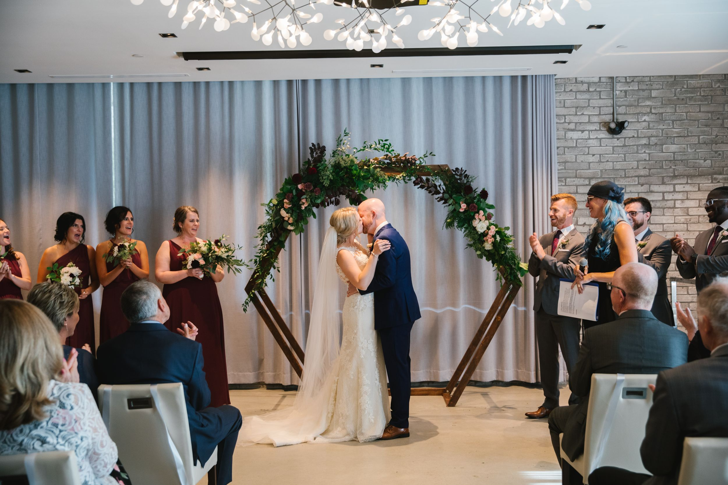 bride and groom first kiss hexagonal wedding arch with greenery indoors