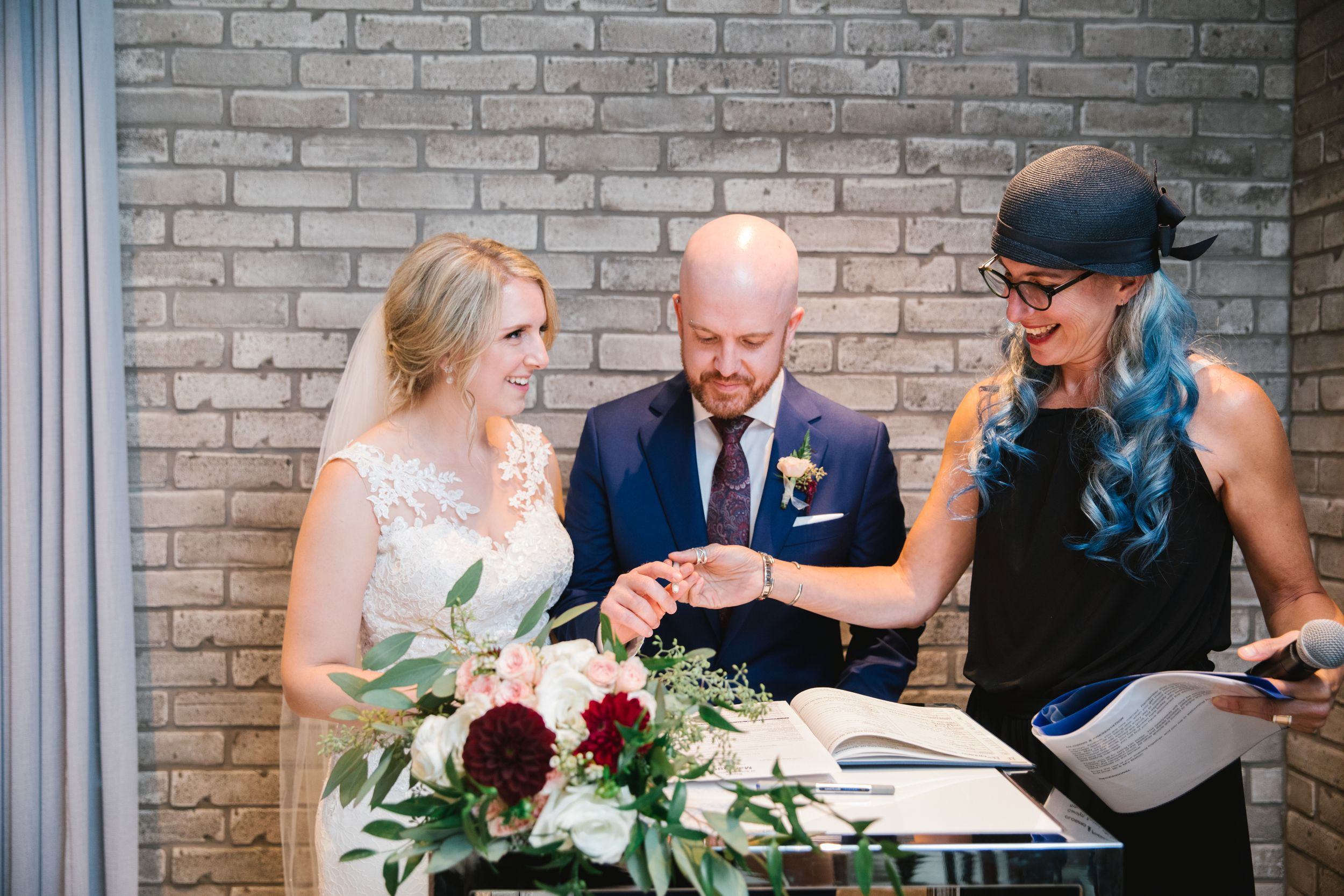bride and groom and officiant with blue hair sign the wedding register toronto