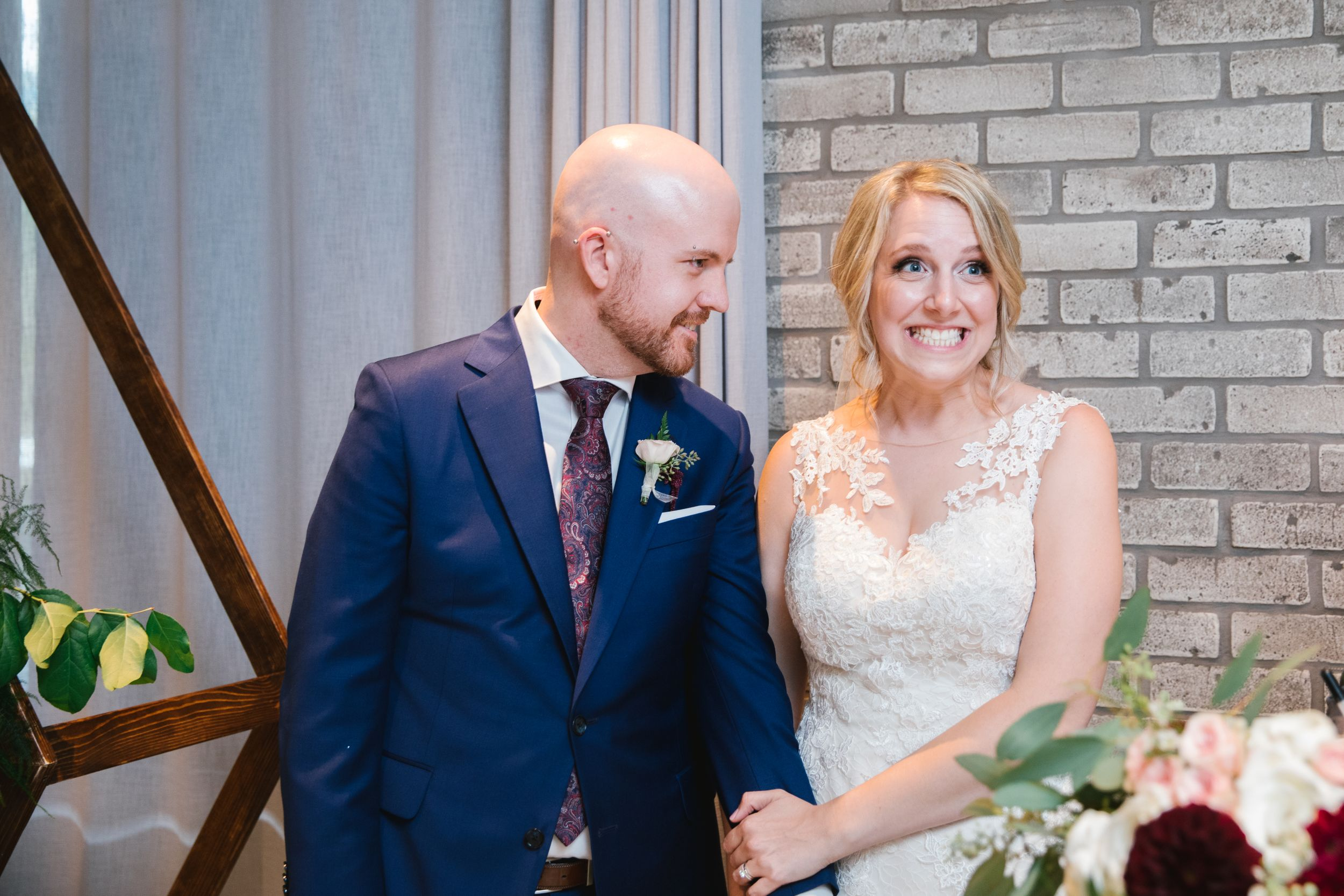 bride pulling a face while groom looks at her and smiles with brick wall behind