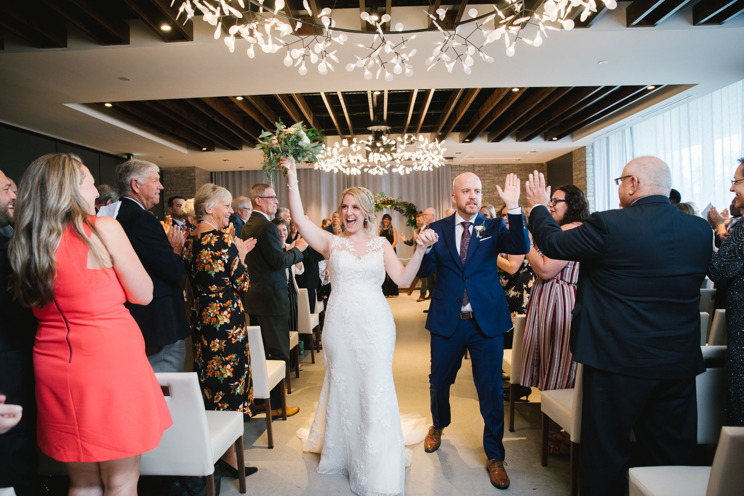 bride and groom celebrate walking down aisle with guests clapping indoors ceremony toronto