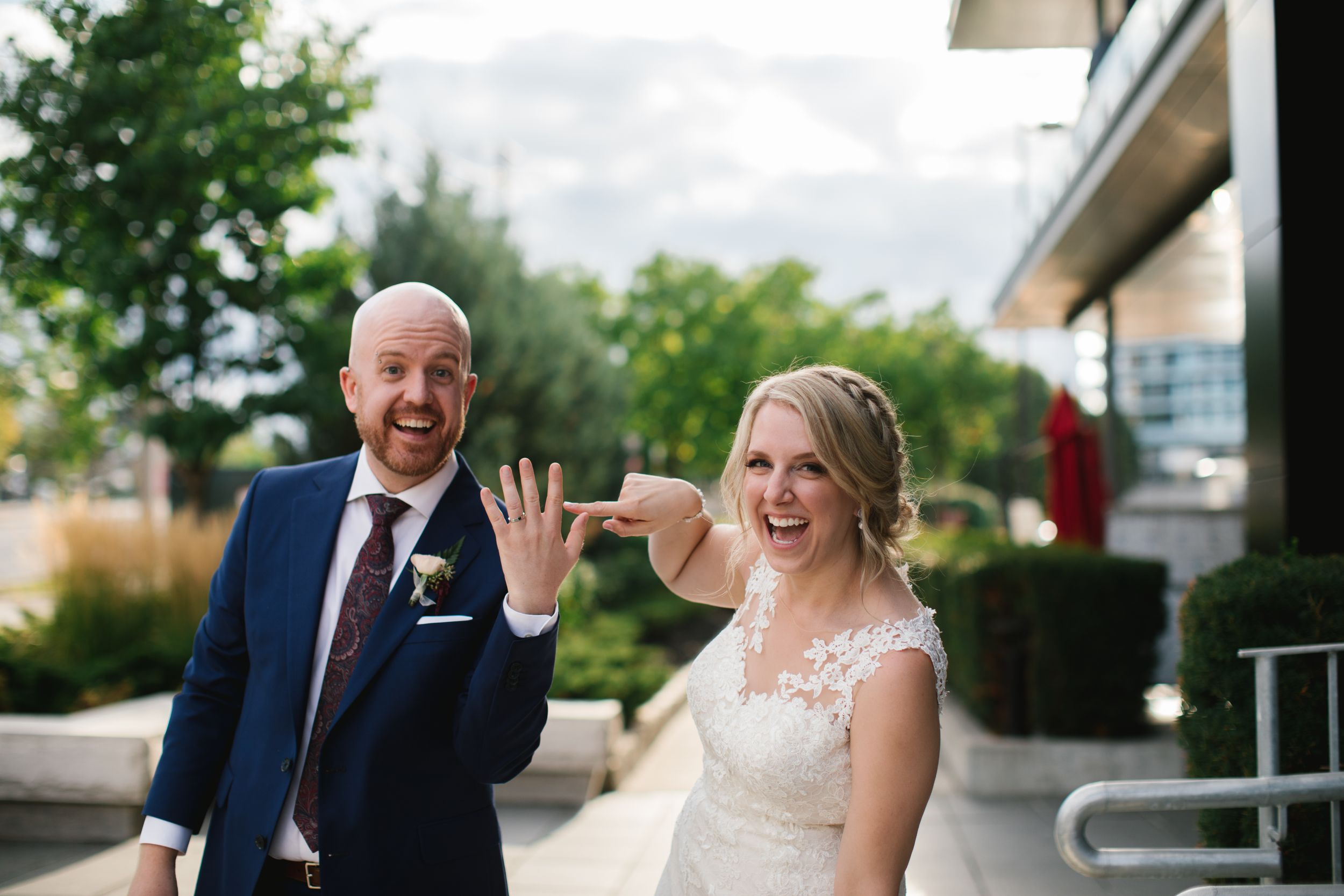 bride laughing and pointing at grooms ring finger