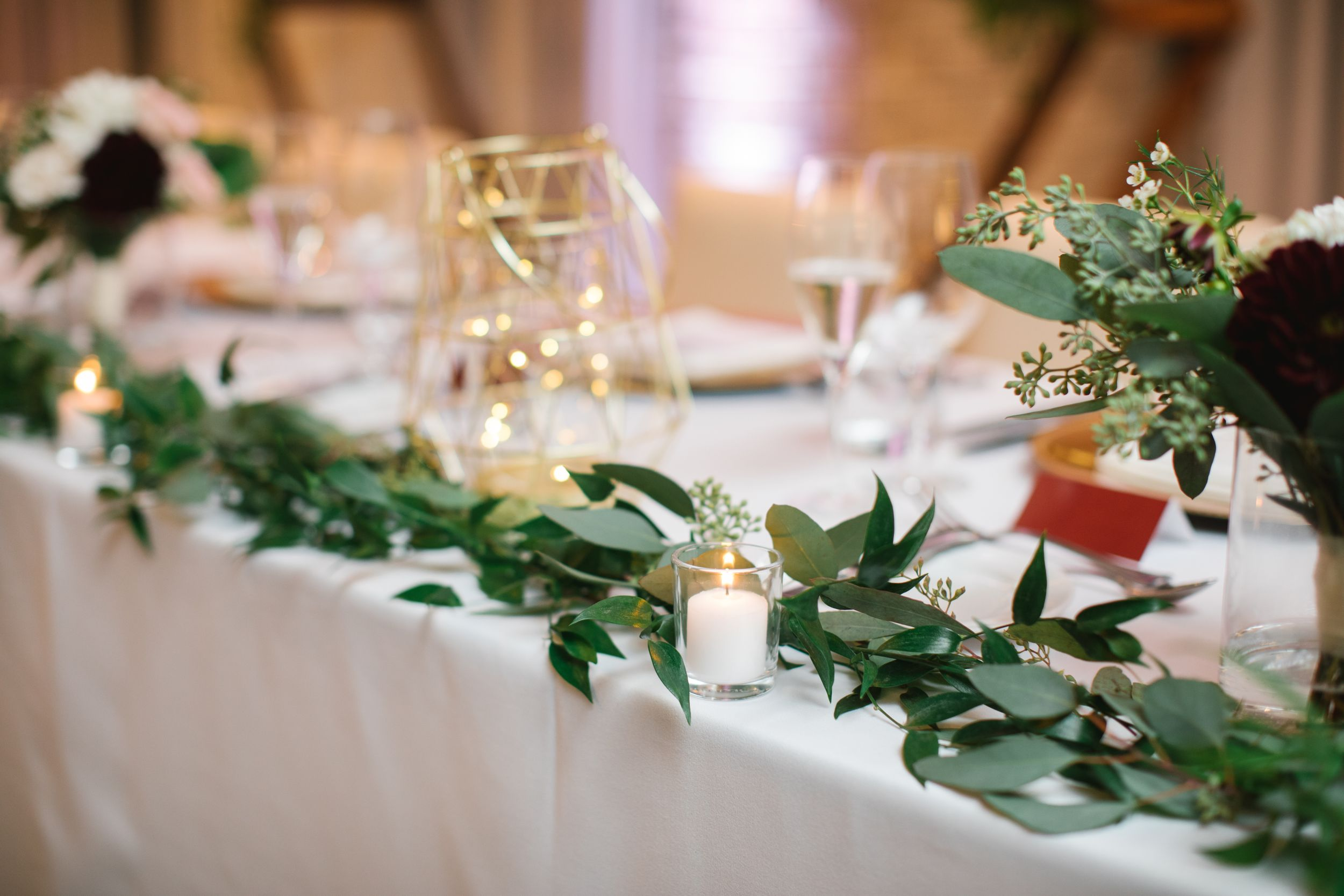 close up of wedding decor candle and greenery table runner head table
