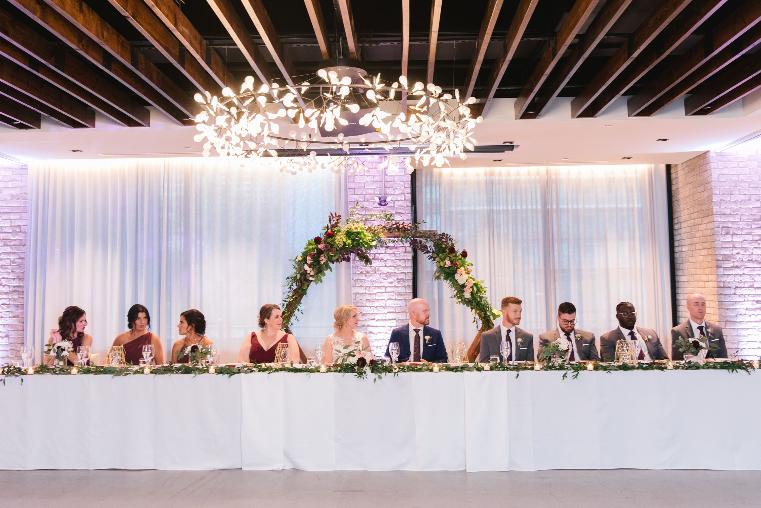 head table with floral arch behind them
