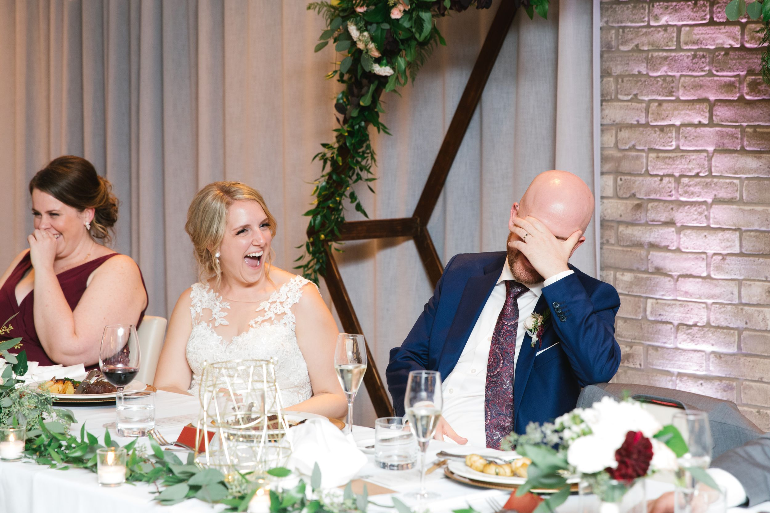 bride laughing and groom covering his face reception best man speech