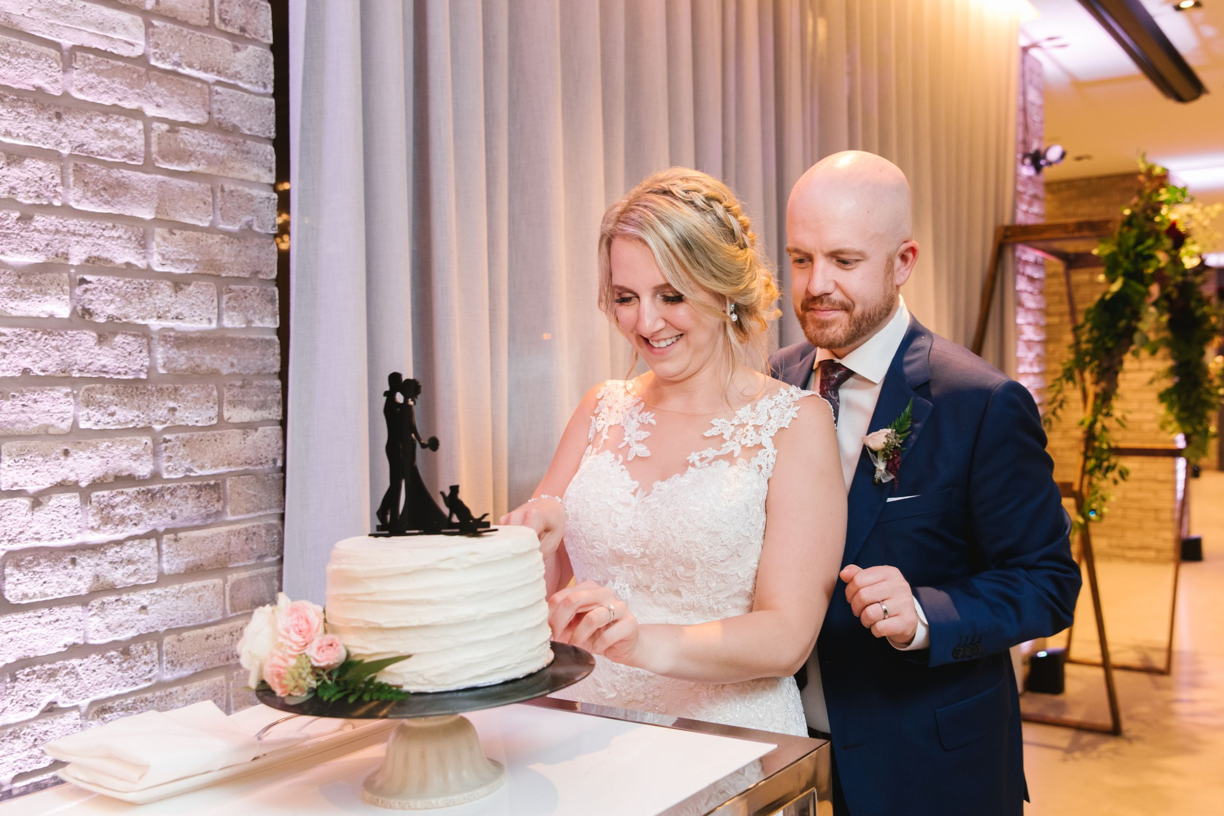 bride and groom cutting small white simple cake