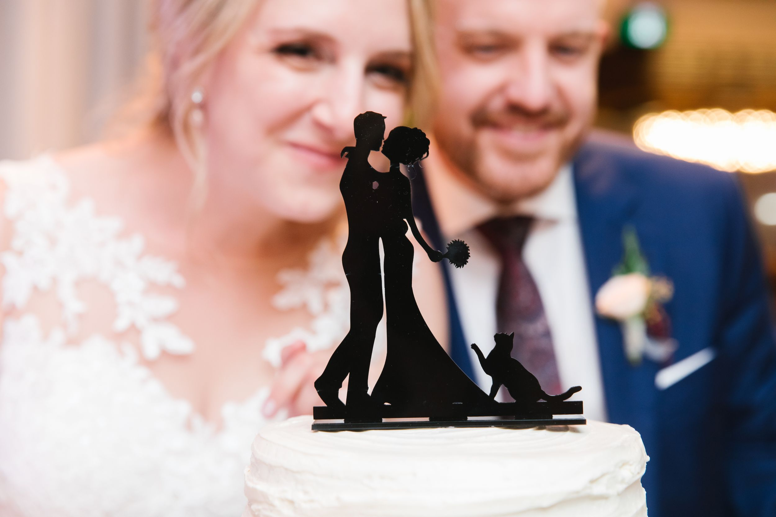 black cut out cake topper with bride and groom in the background