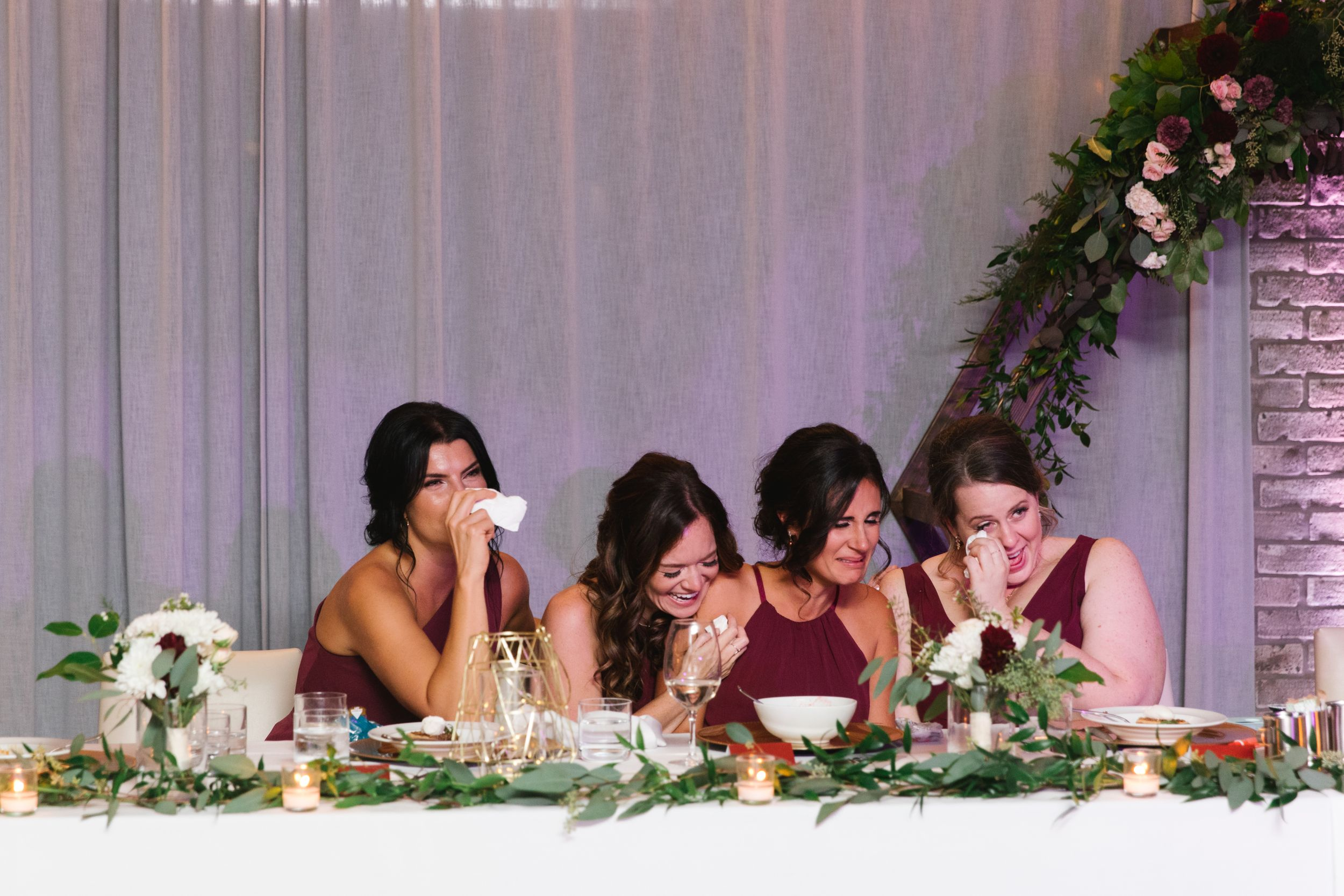 four bridesmaids crying and holding tissues during first dance