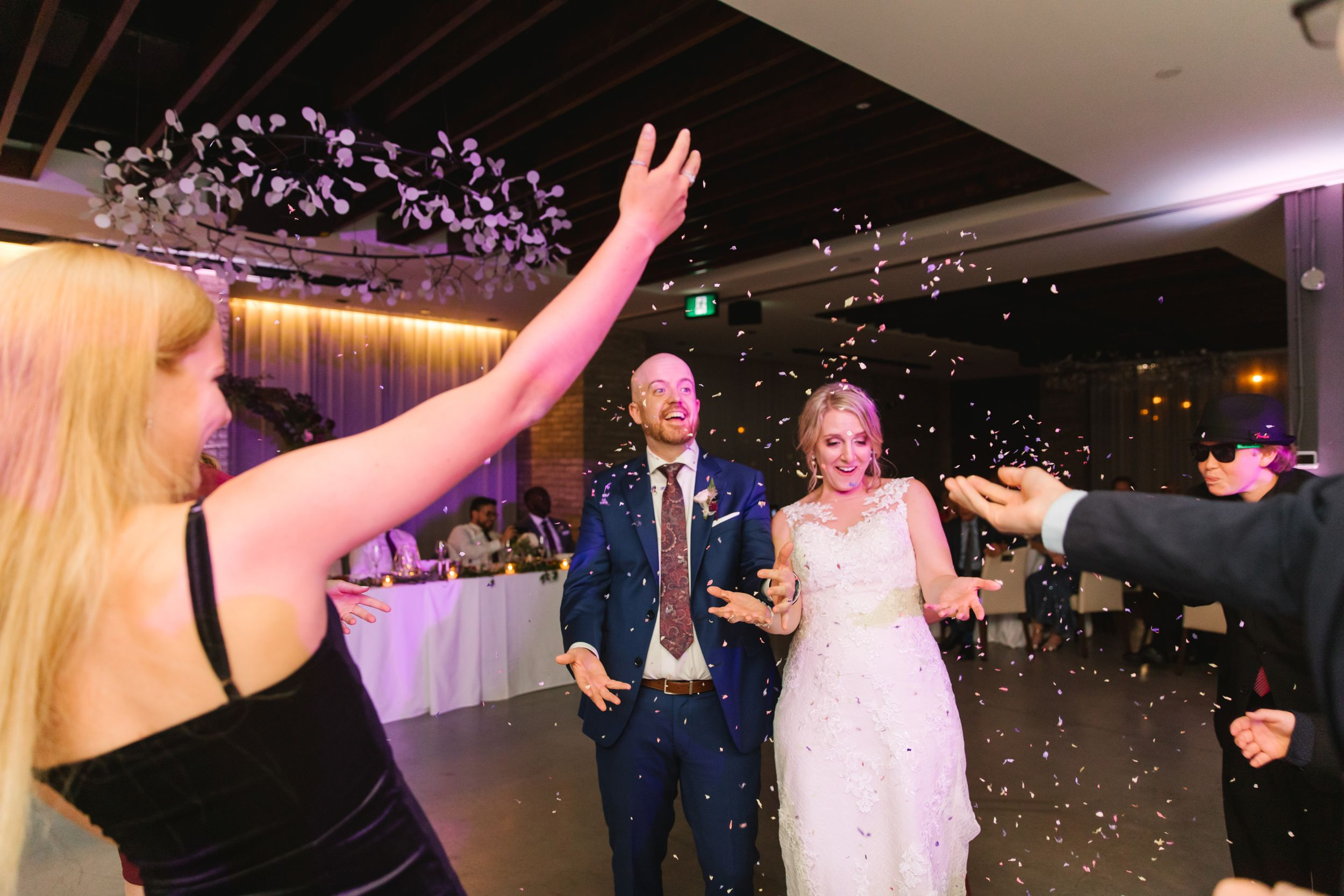 guests throw confetti on bride and groom who are surprised at reception
