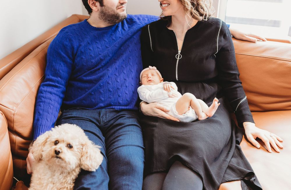 Parents sitting on the sofa with dog holding newborn during their Chicago Lifestyle newborn session
