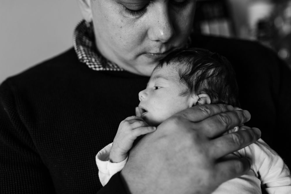 Dad holding baby girl on his chest Chicago newborn lifestyle session