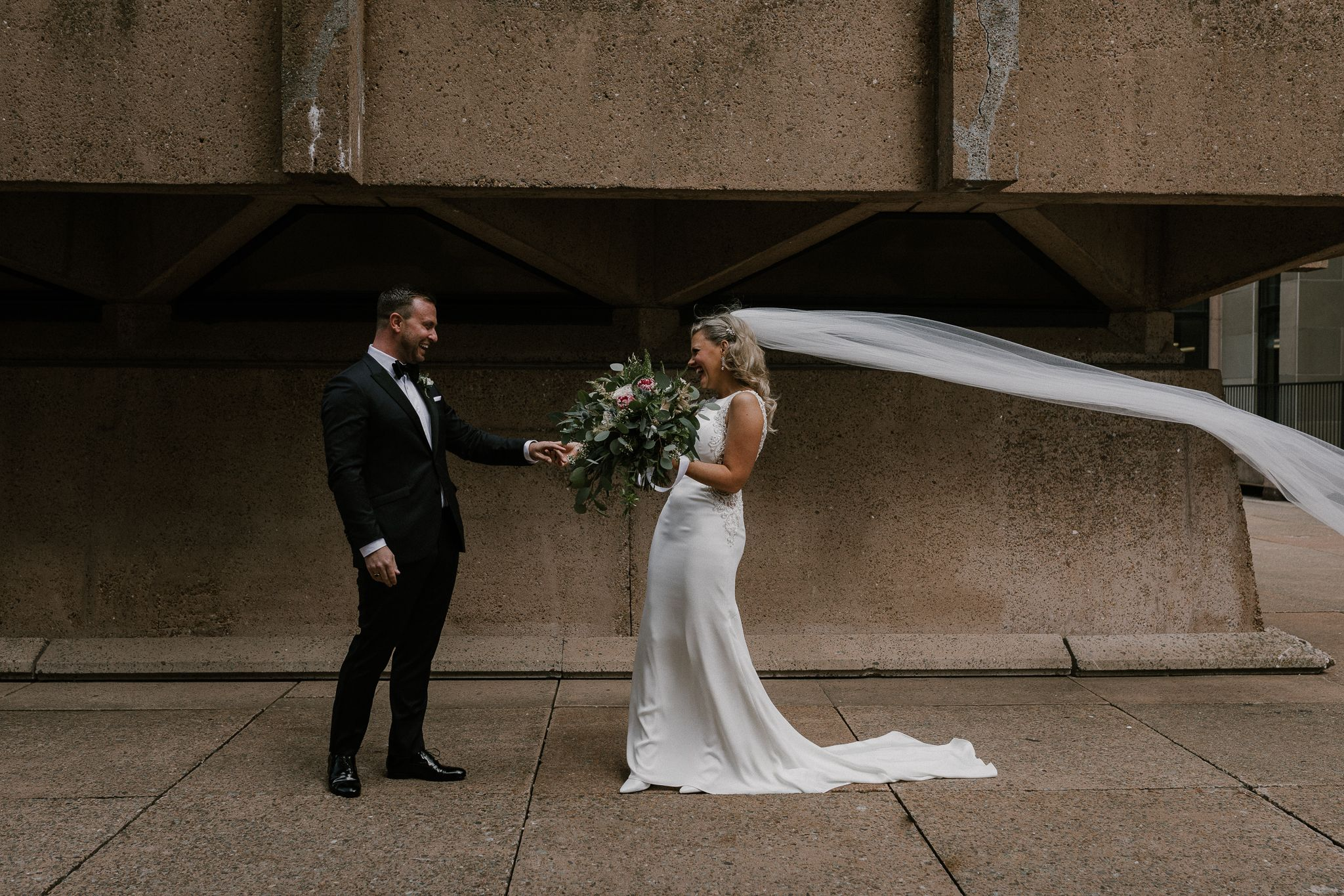 Bride and groom during first look at PEI Confederation Center with the bride's veil flowing in the wind.