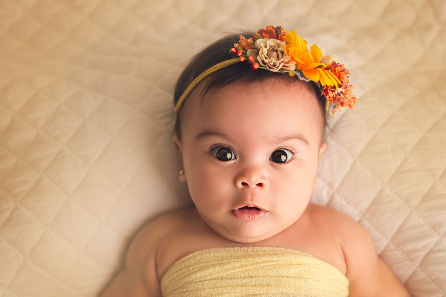 baby girl close up with floral headband yellow