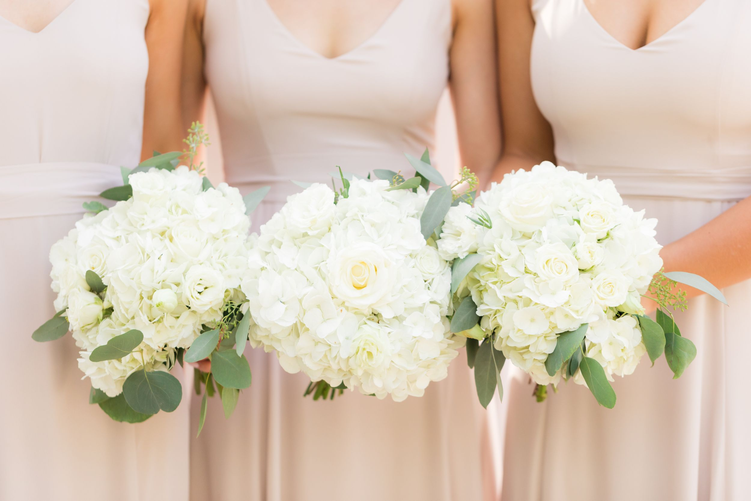 Bridesmaid in blush hold their white rose bouquets together.