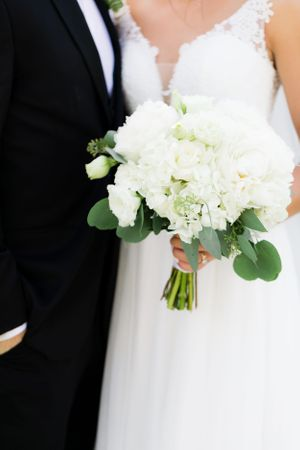 White rose bridal bouquet with greenery.