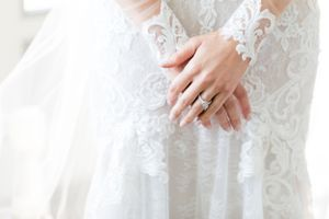 Bride holds her hands while getting ready, and shows her wedding ring.