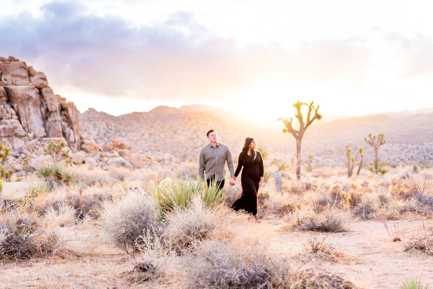 woman in black dress holds man's hand and leads him through Joshua Tree National Park at sunset for engagement pictures