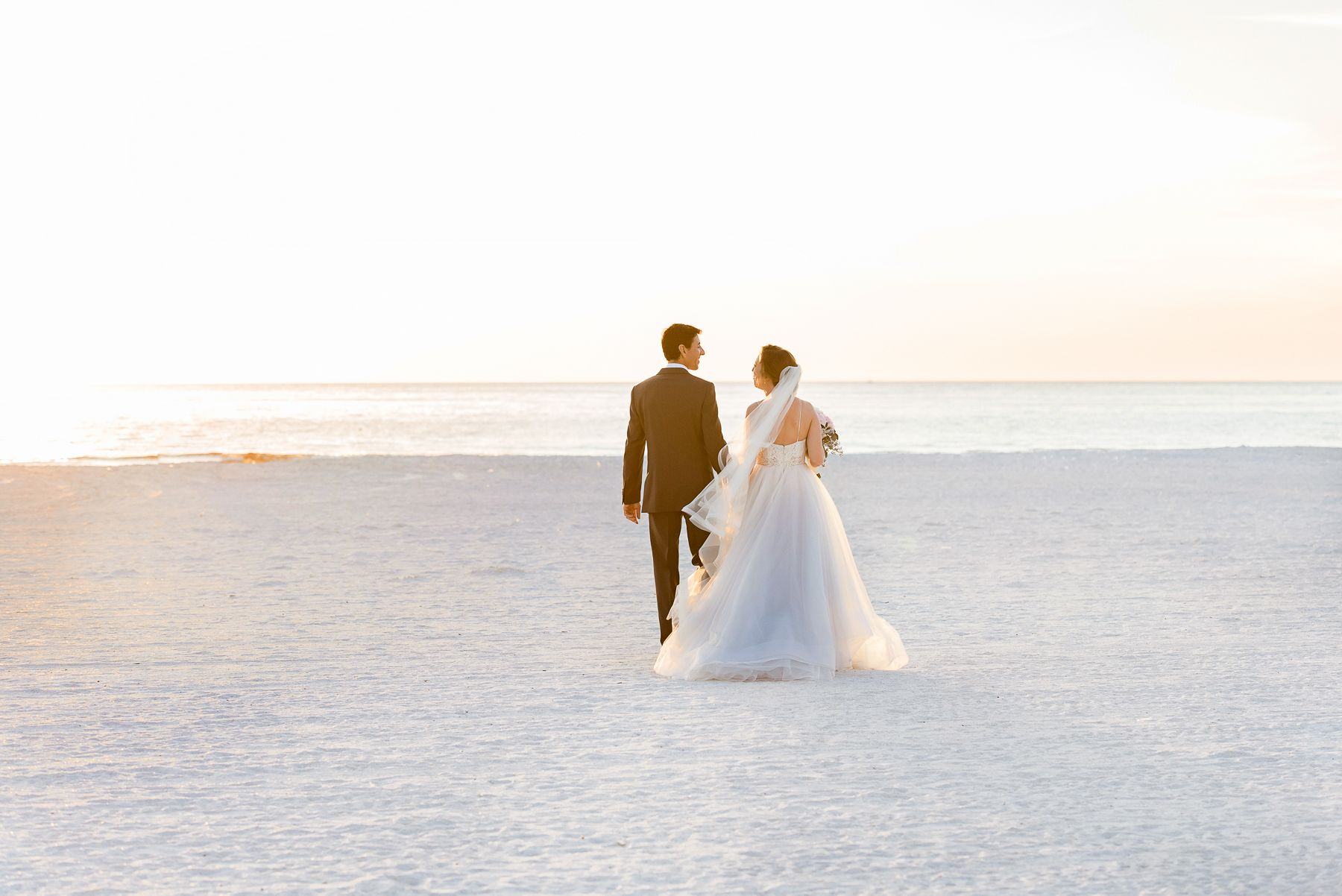 bride and groom walking on the beach at sirata beach resort wedding in st pete