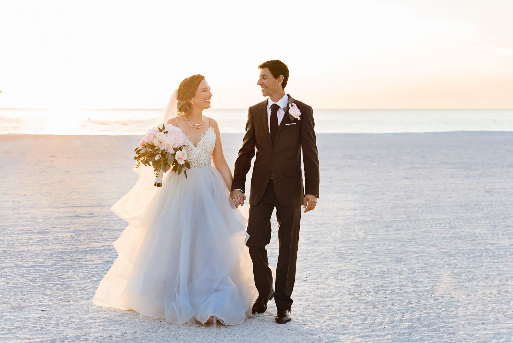 bride and groom walking on beach at sirata beach resort wedding in st pete florida