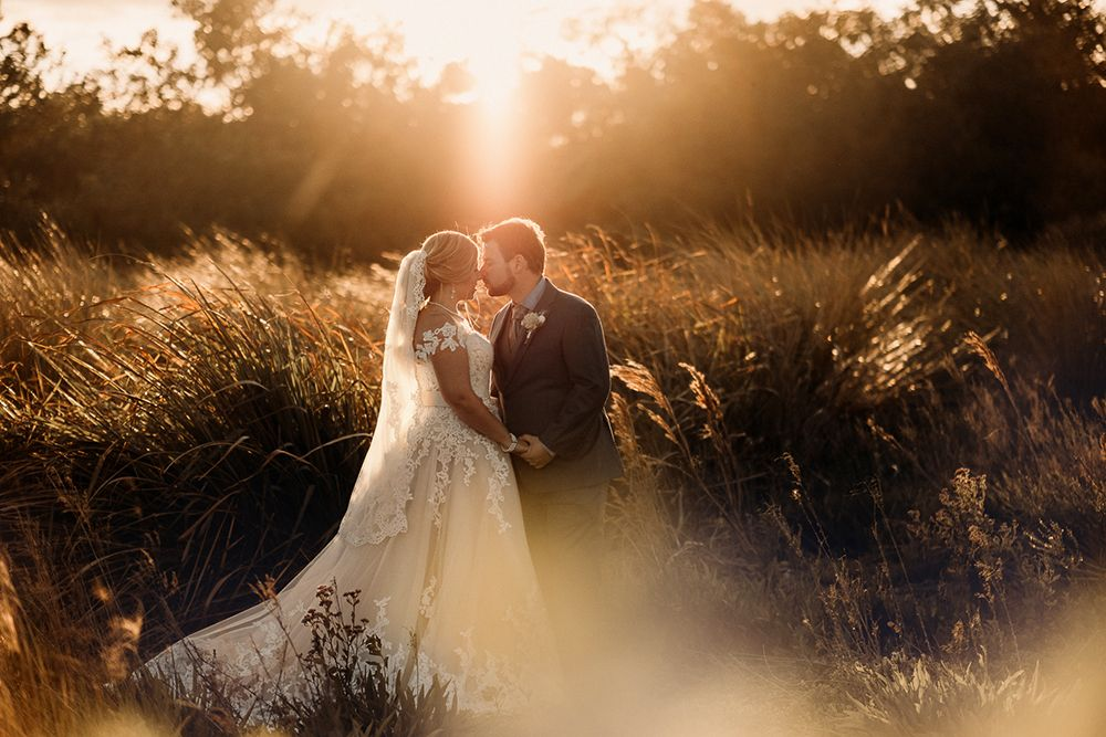 Bride and Groom Kissing in Field by Bradenton Wedding Photographer