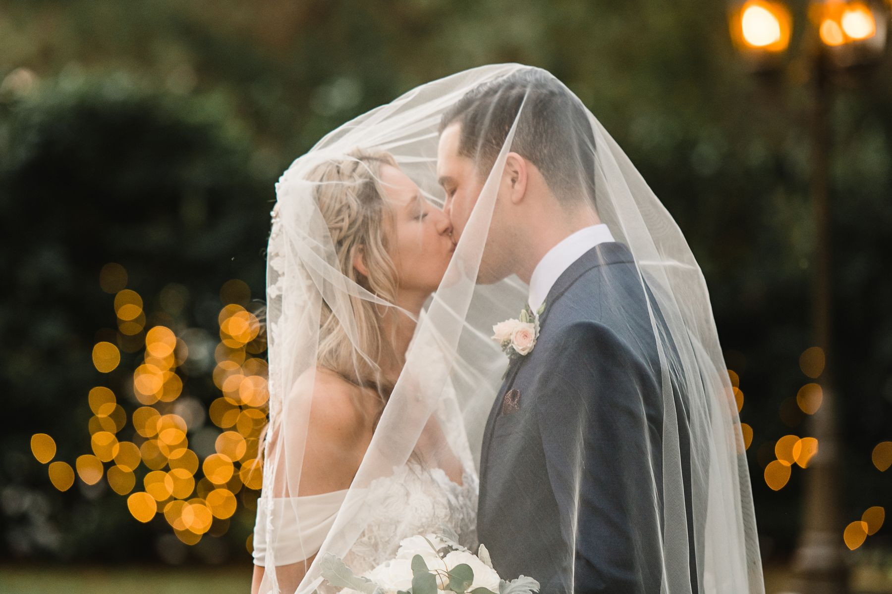 couple kissing under veil at baker's ranch wedding, tampa, fl