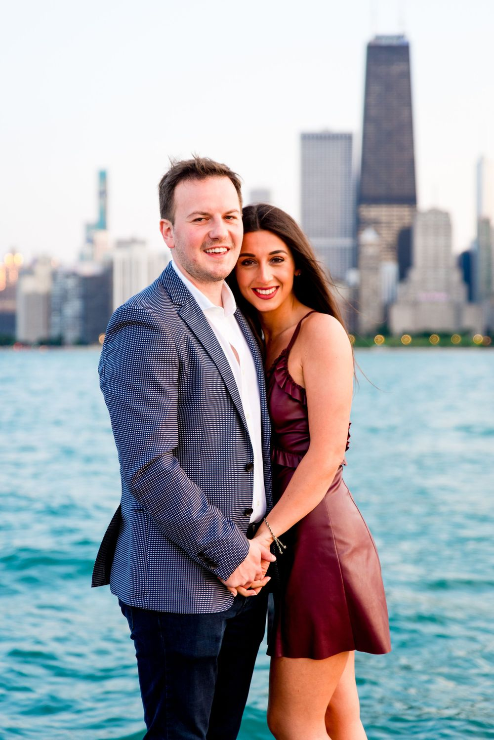 man and woman holding hands looking at camera in front of Chicago skyline + Lake Michigan after North Ave Beach proposal