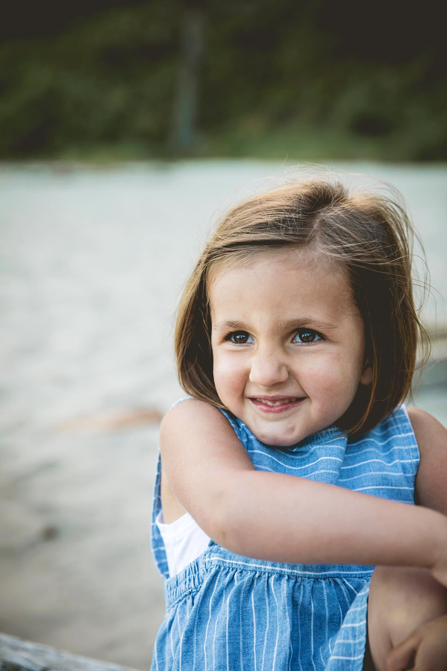 toddler girl looking off to the side, smiling while at the beach